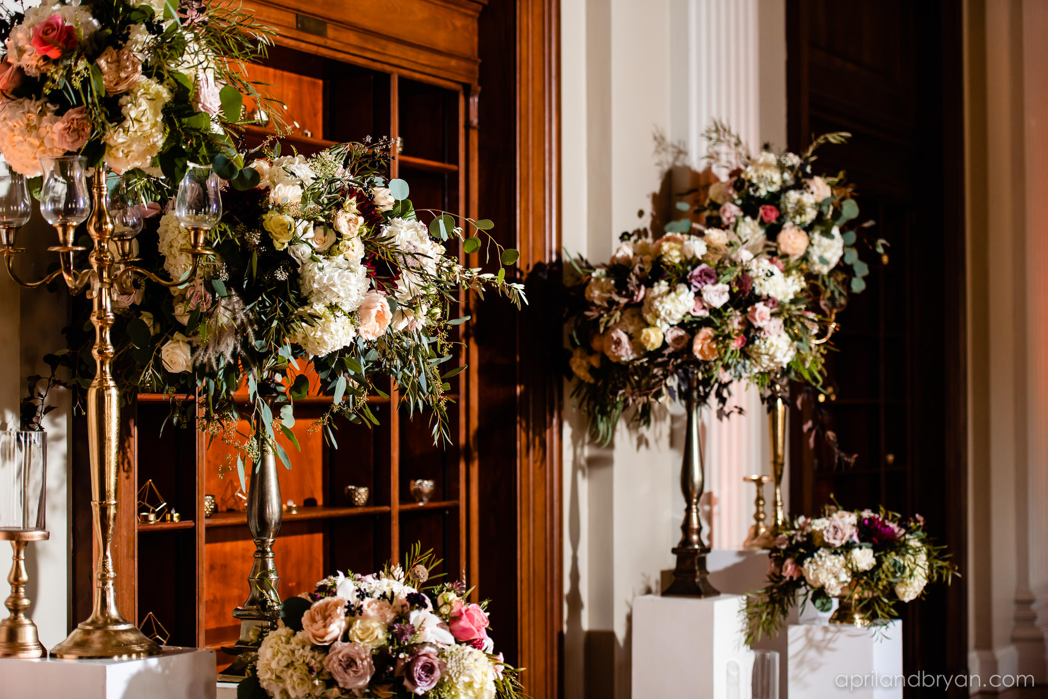 Blush pink and white flowers paired with greenery frame the Franklin Institute ceremony photographed by April & Bryan Photography. Featured on Dream Weddings.