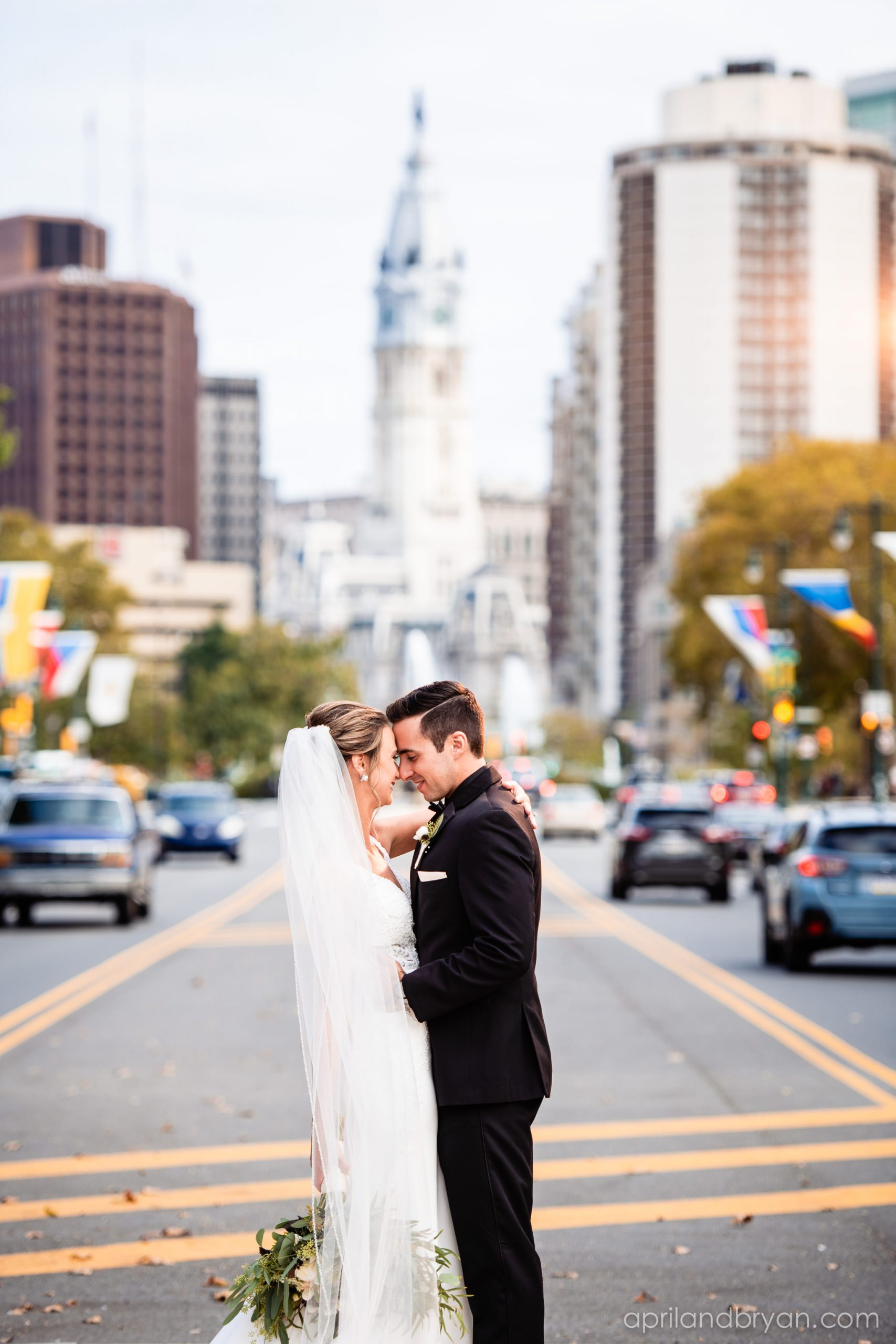 Newlyweds pose for April & Bryan Photography on Broad Street in Philadelphia, PA. Featured on Dream Weddings.