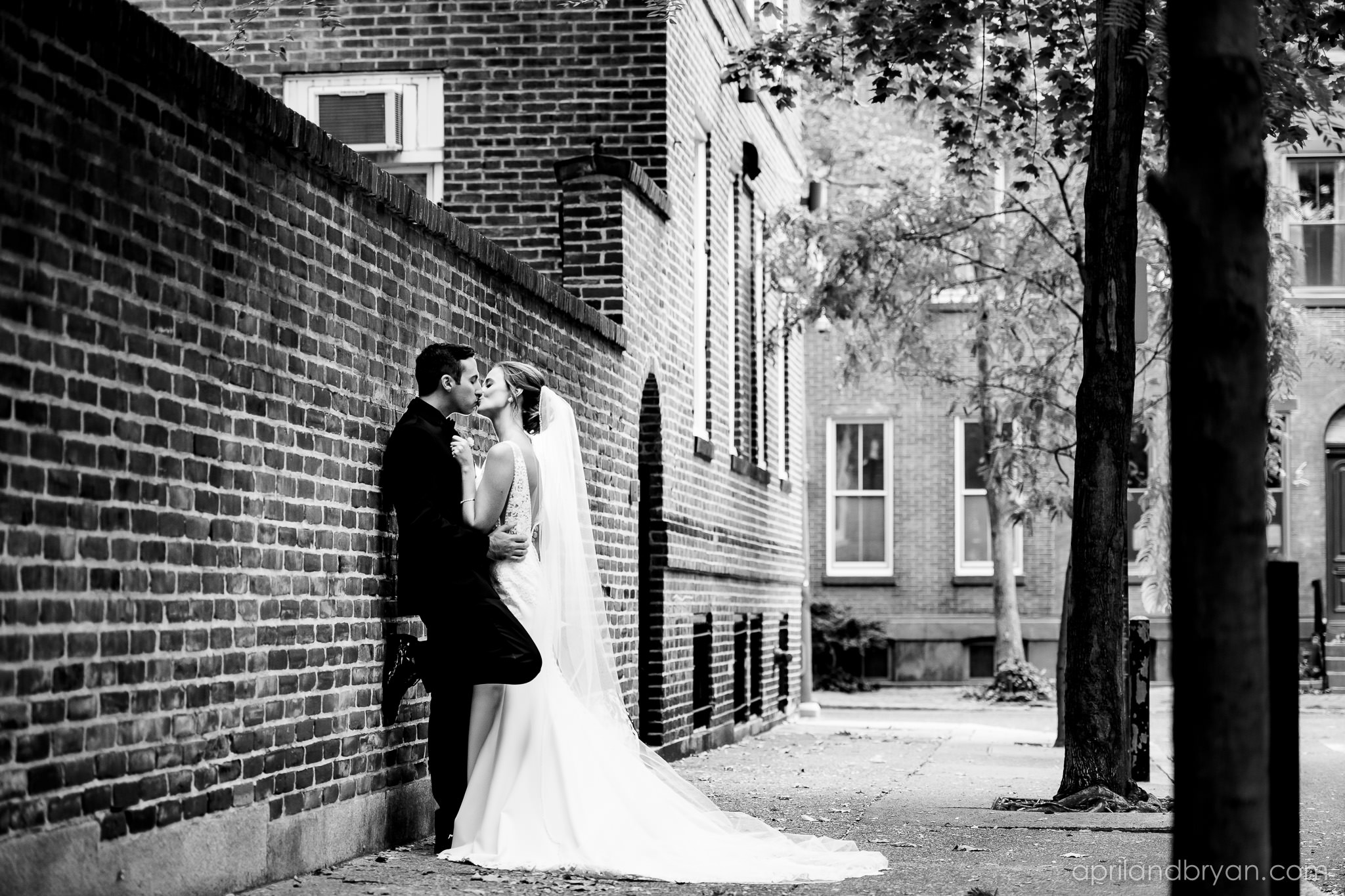 Husband and bride share a kiss on the streets outside of the frANKLIN institute of Philadelphia. Shot by April & Bryan Photography. Featured on Dream Weddings.