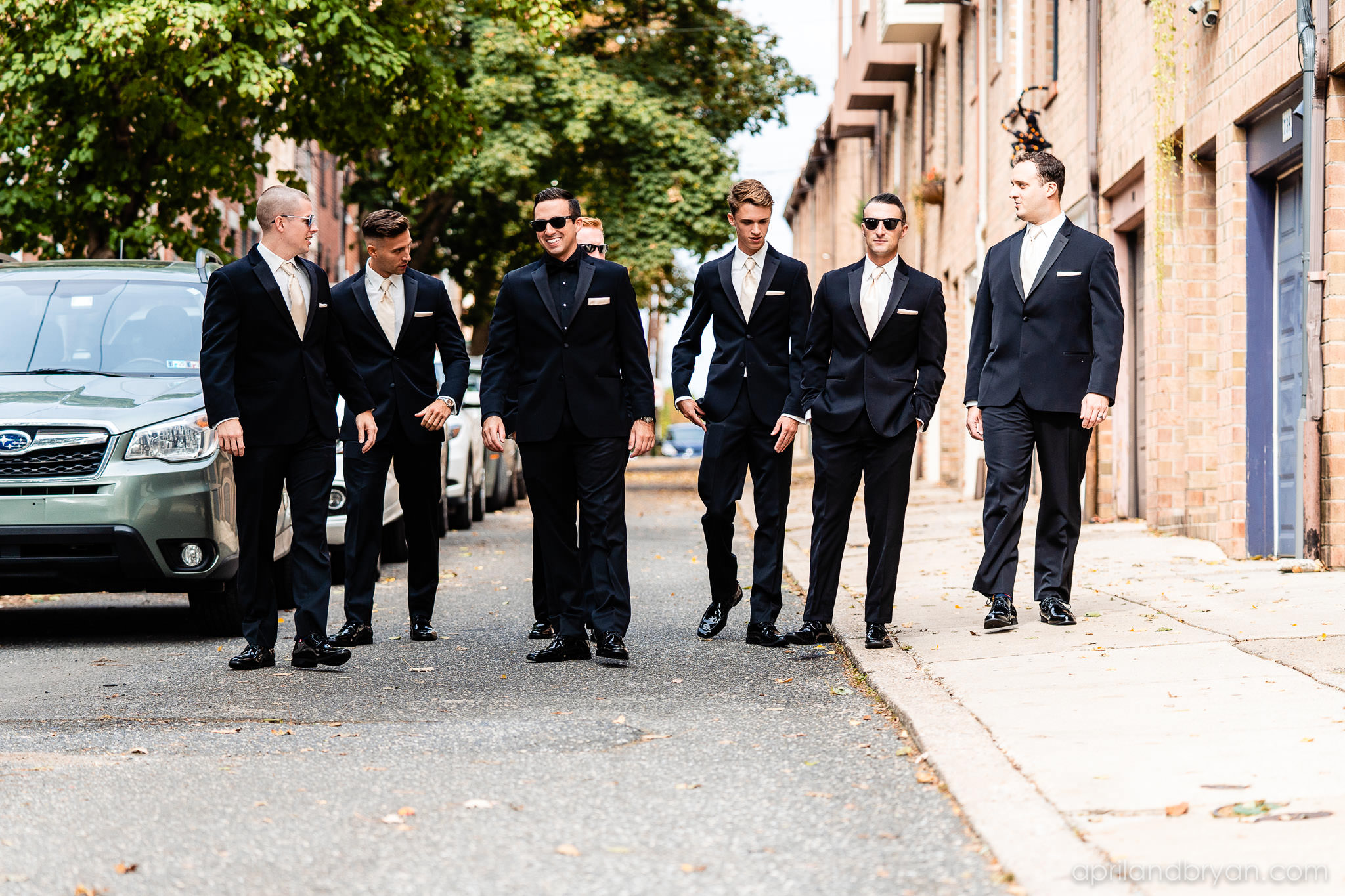 The groomsmen take a stroll before the ceremony at the Franklin Institute in Philadelphia, PA. Shot by April & Bryan Photography. Featured on Dream Weddings.