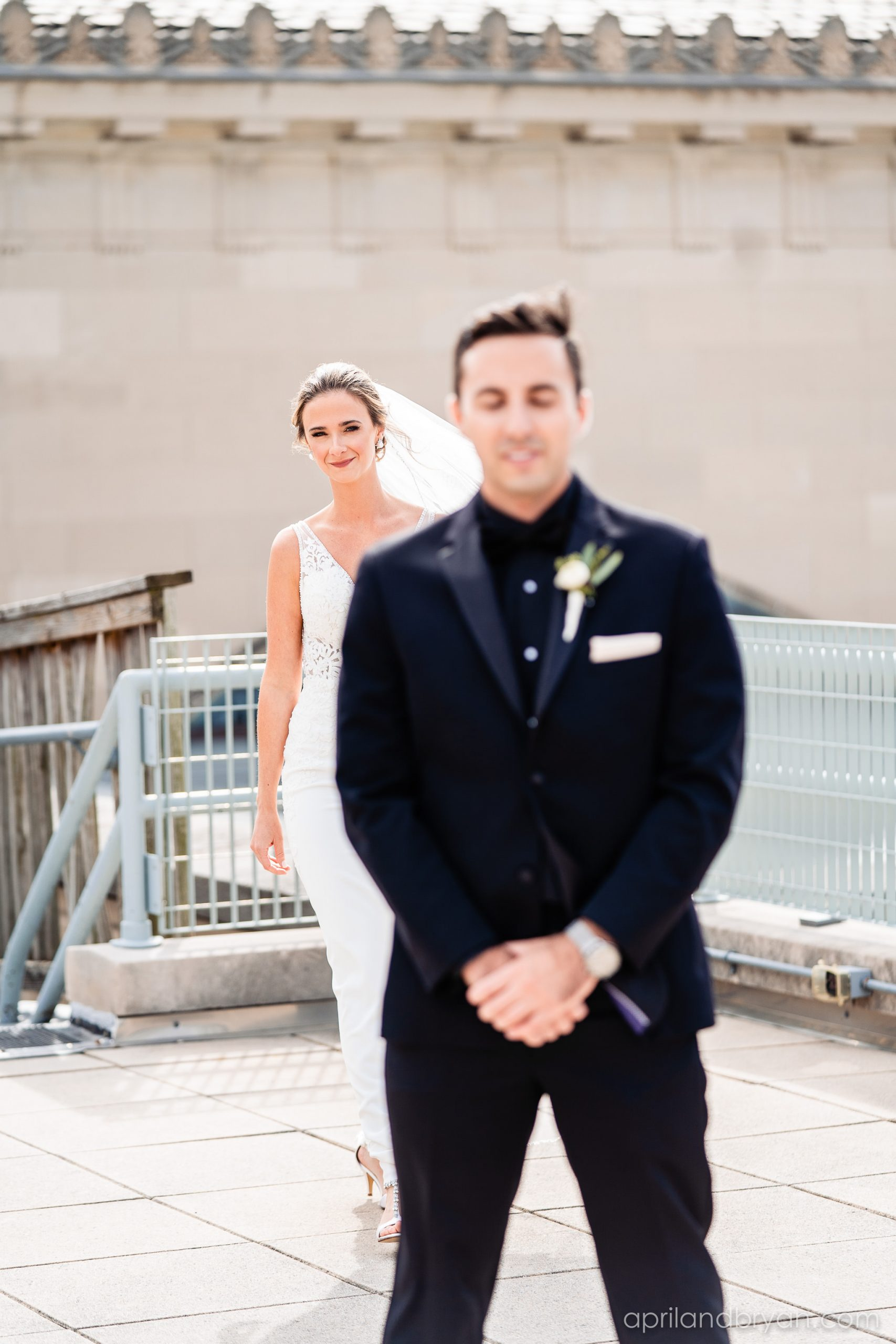 The groom patiently awaits the first look of his blushing bride on the roof of the Franklin Institute in Philadelphia. This moment was captured by April & Bryan Photography. Featured on Dream Weddings..