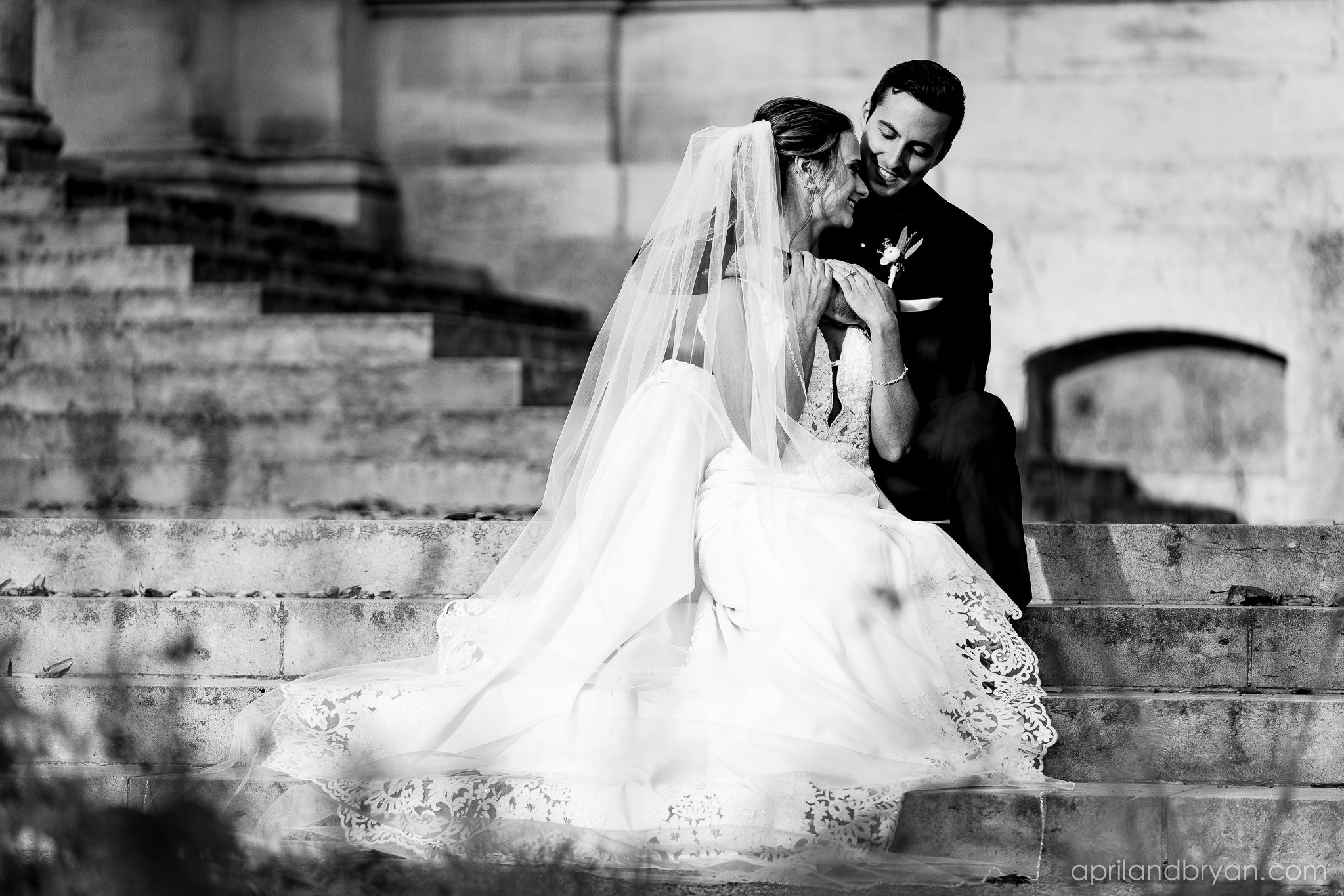 the loving couple pose on the steps of the Franklin Institute in Philadelphia, PA. Shot by April & Bryan Photography. Featured on Dream Weddings.