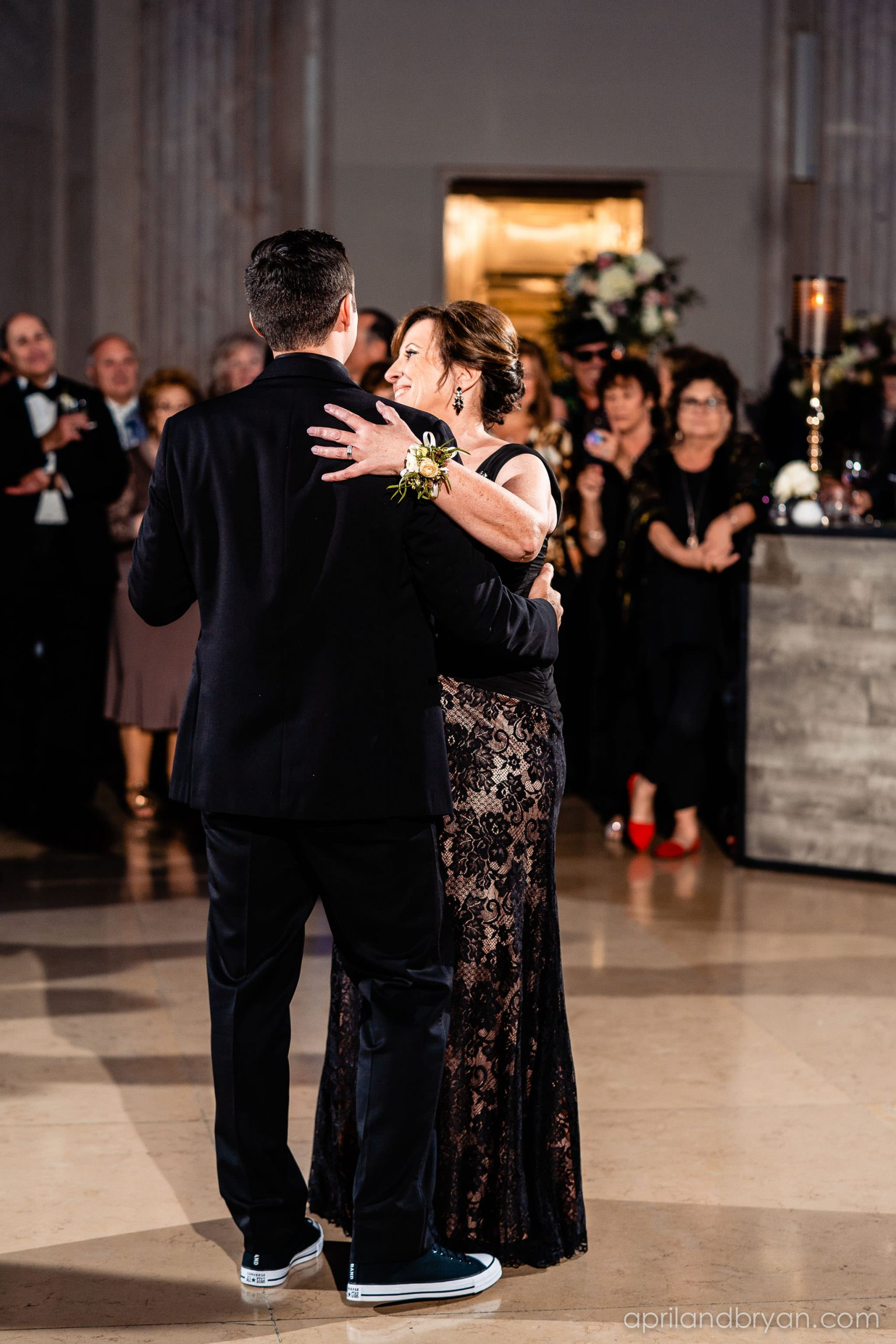A mother and son dance, featuring some Chucks started off the celebration at the Franklin Institute in Philadelphia. Captured by April & Bryan Photography. Featured on Dream Weddings.