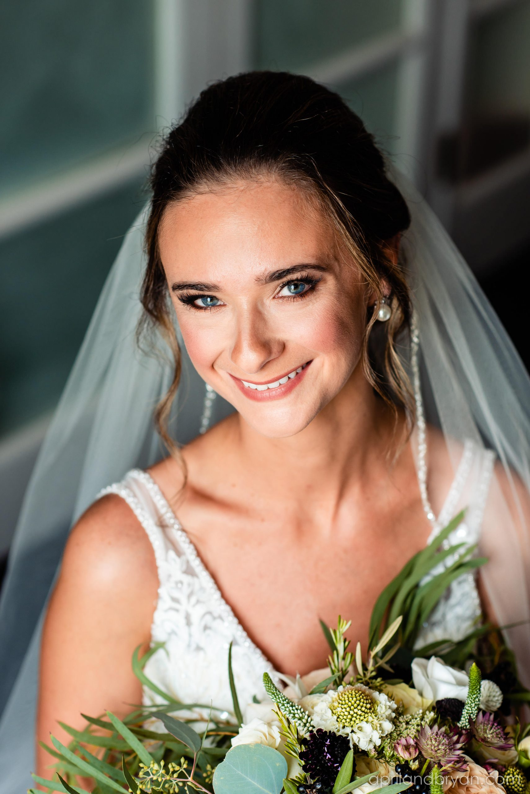 A close-up of the bride and her greenery in her bouquet are captured perfectly by April & Bryan Photography nat the Franklin Institute located in Philadelphia, PA.