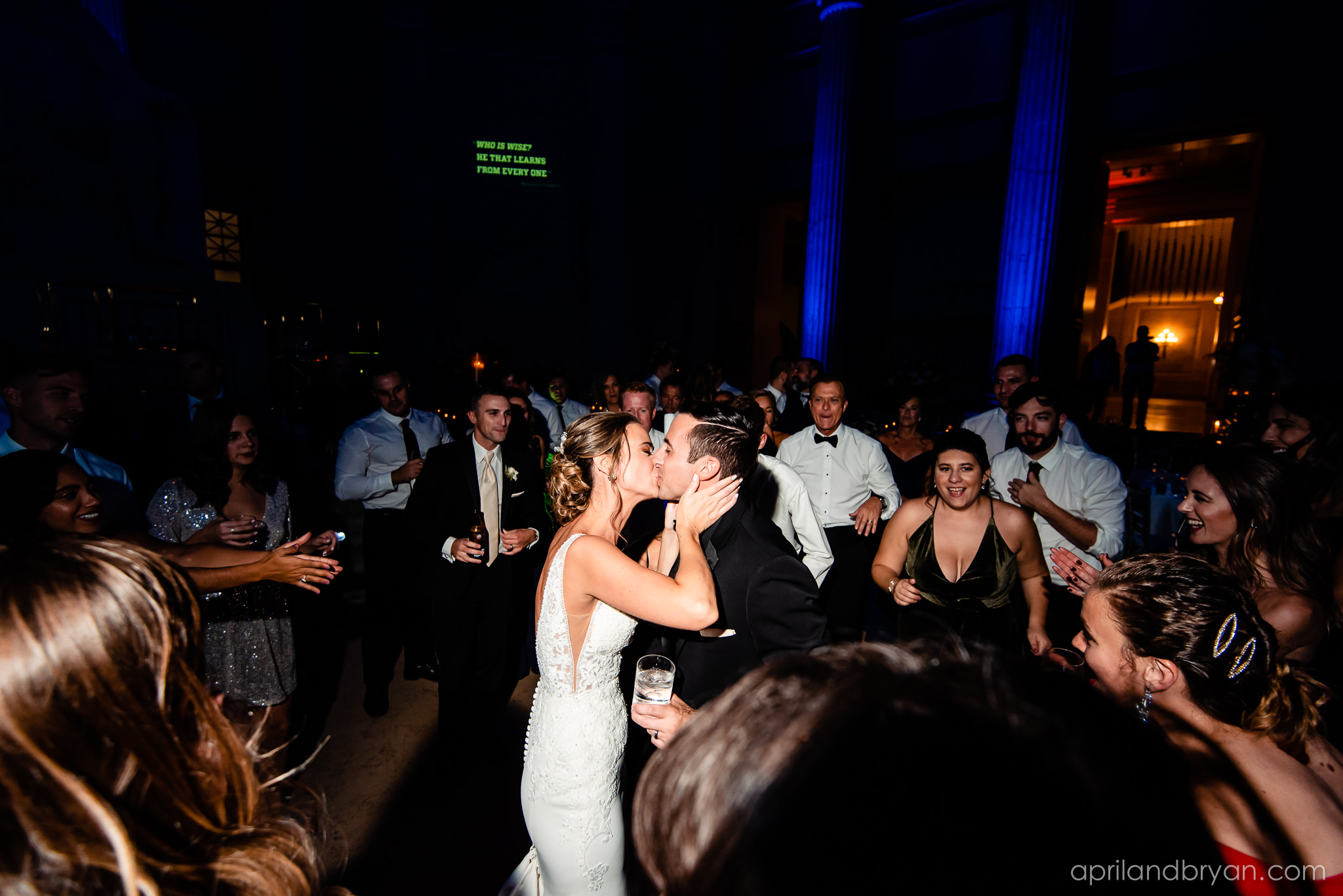 A celebratory kiss made by the newlyweds at the Franklin Institute, captured by April & Bryan Photography. Featured on dream Weddings.