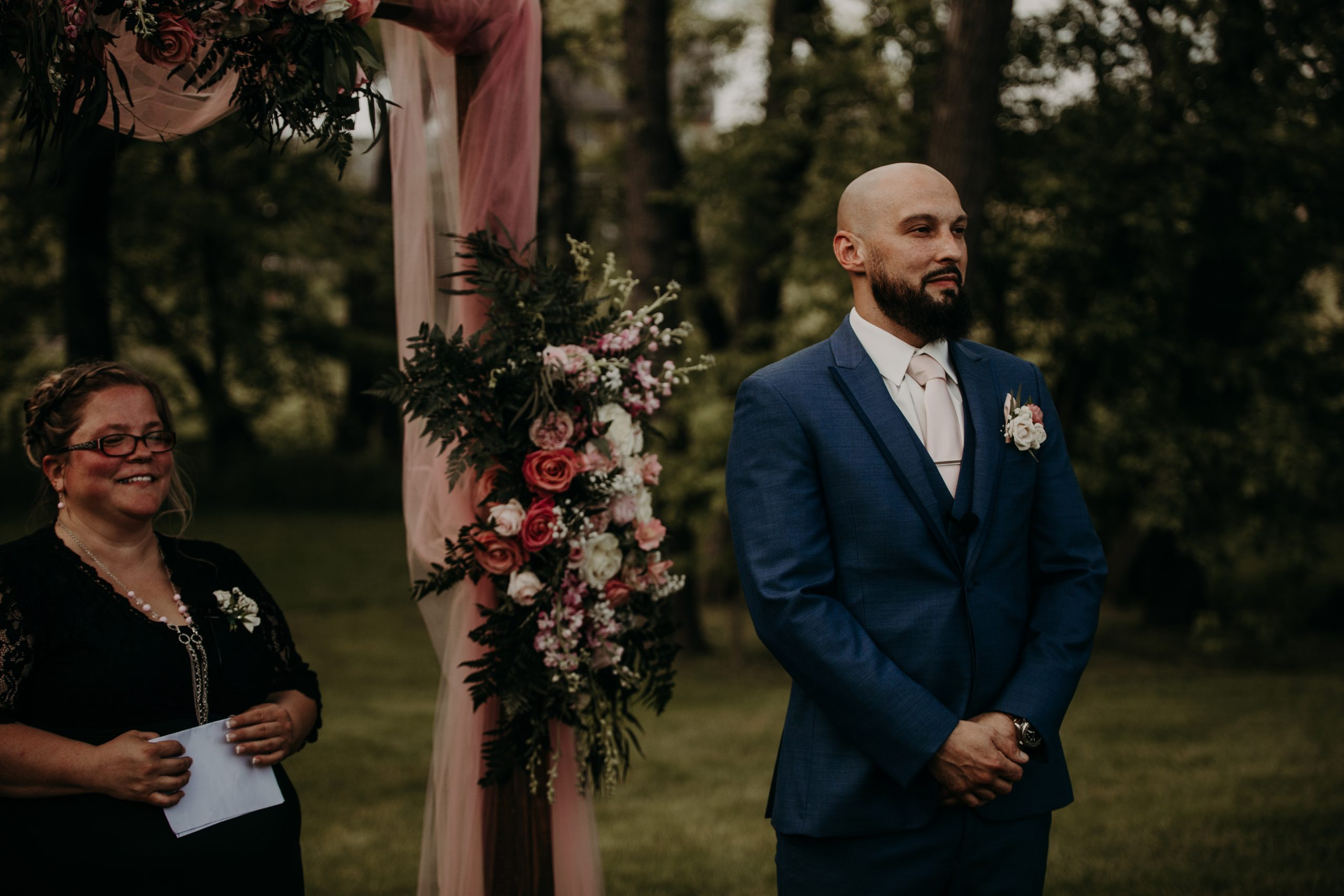 Richard awaits the ceremony to begin at the end of the isle. Christine and Richard wed on the Chestnut Hill Villa grounds on May of 2019. This organic ethereal styled wedding was captured by Garnet Dahlia Photography and featured on Dream Weddings.