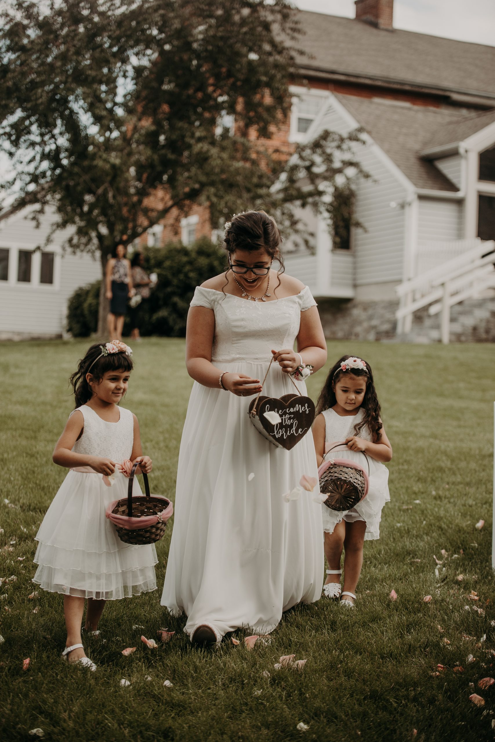 the flower girls kickstart the ceremony with petals thrown all about the green grass. Christine and Richard wed on the Chestnut Hill Villa grounds on May of 2019. This organic ethereal styled wedding was captured by Garnet Dahlia Photography and featured on Dream Weddings.