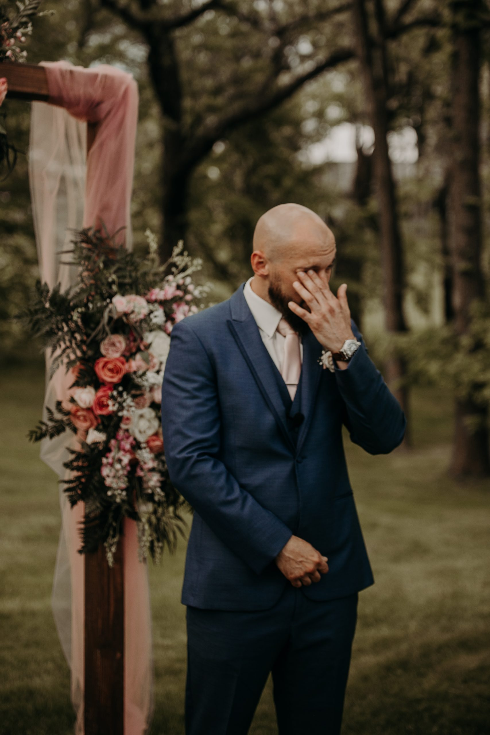 Richard is overcome with emotion as his bride makes her way down the isle. Sporting a blue suite and a pastel pink tie, the groom is ready to say I do. Christine and Richard wed on the Chestnut Hill Villa grounds on May of 2019. This organic ethereal styled wedding was captured by Garnet Dahlia Photography and featured on Dream Weddings.
