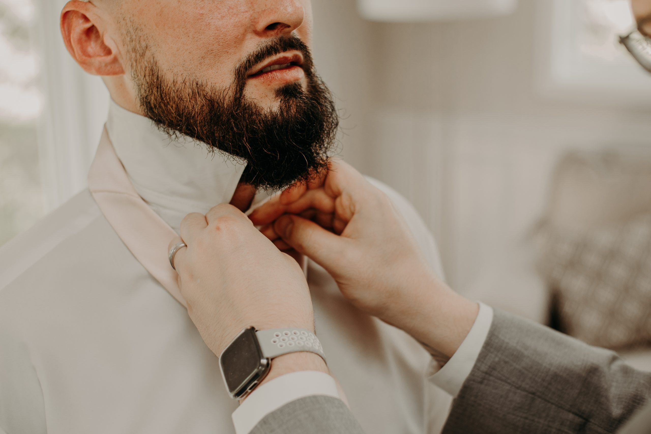 A groomsmen helps Richard with ihs tie before the ceremony begins. Christine and Richard wed on the Chestnut Hill Villa grounds on May of 2019. This organic ethereal styled wedding was captured by Garnet Dahlia Photography and featured on Dream Weddings.