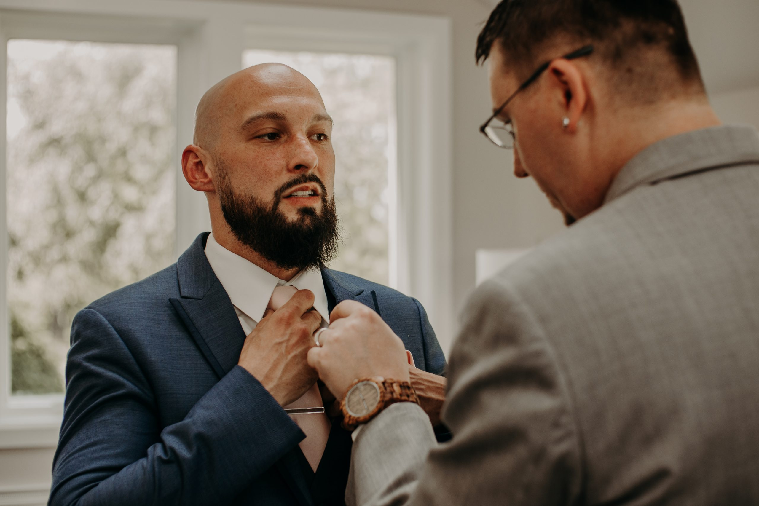 Getting some help from the groomsmen, the groom wraps up and finishing touches to his wardrobe that he will wear while walking down the isle. Christine and Richard wed on the Chestnut Hill Villa grounds on May of 2019. This organic ethereal styled wedding was captured by Garnet Dahlia Photography and featured on Dream Weddings.