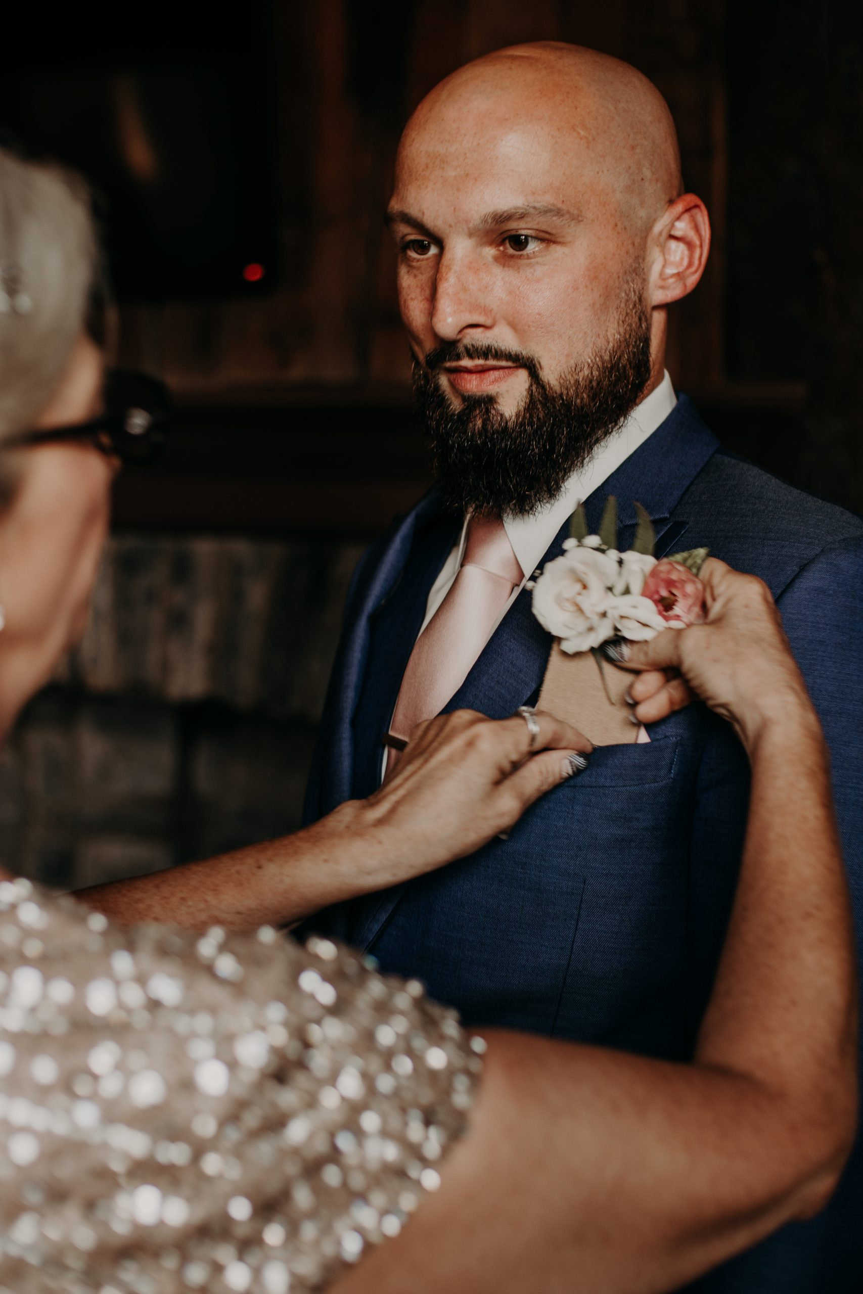 The grooms mother pins his corsage to the pocket of his navy blue jacket. Christine and Richard wed on the Chestnut Hill Villa grounds on May of 2019. This organic ethereal styled wedding was captured by Garnet Dahlia Photography and featured on Dream Weddings.