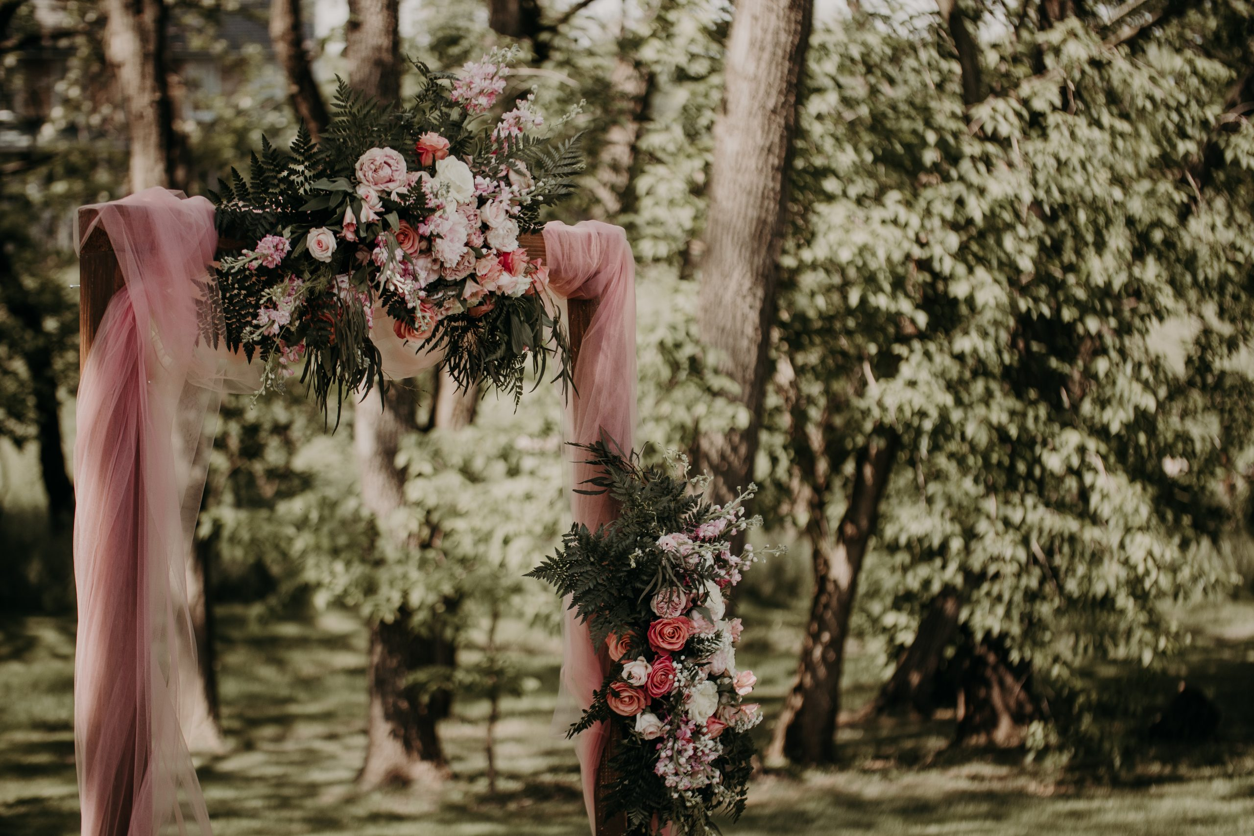 A rustic wooden archways adorned with pink and white flowers is soon to frame the newly wedded couple. Christine and Richard wed on the Chestnut Hill Villa grounds on May of 2019. This organic ethereal styled wedding was captured by Garnet Dahlia Photography and featured on Dream Weddings.