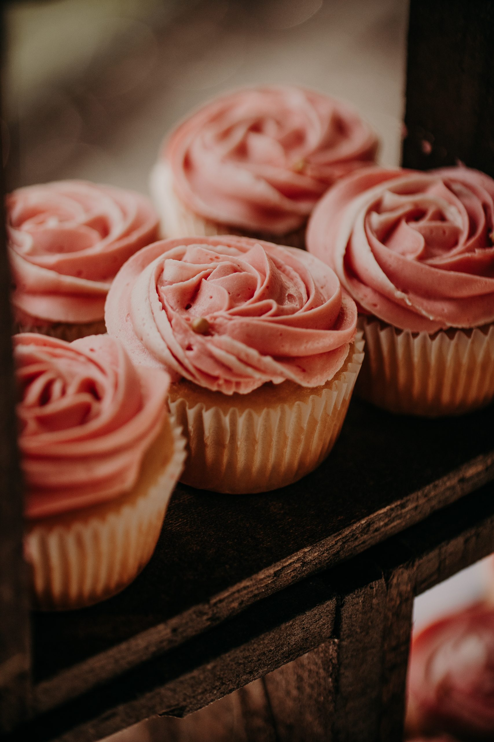 Blush pink cupcakes are placed around the matching cake. Christine and Richard wed on the Chestnut Hill Villa grounds on May of 2019. This organic ethereal styled wedding was captured by Garnet Dahlia Photography and featured on Dream Weddings.