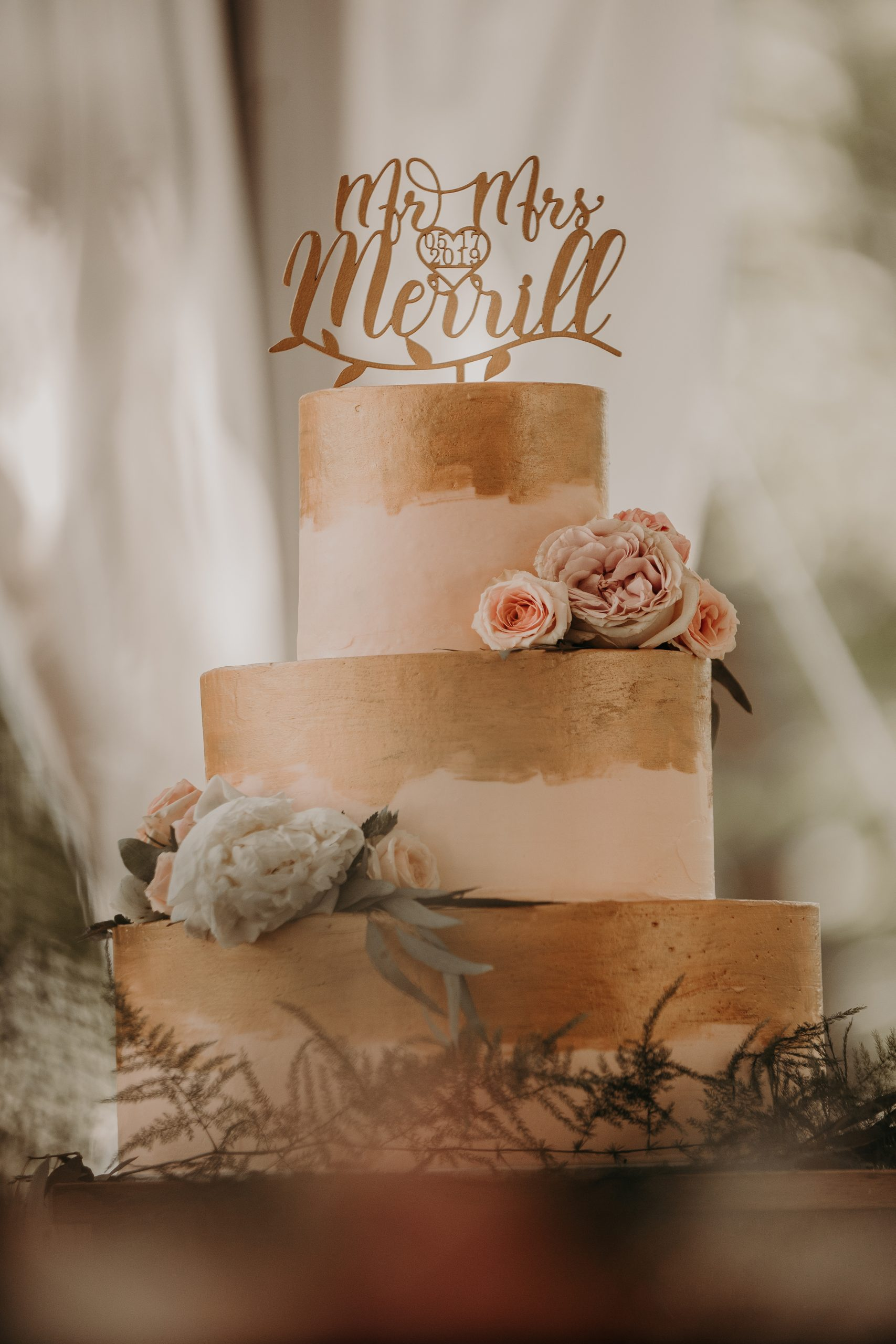 A lovely cake accented with gold paint with blush pink fondant. Mr. and Mrs. Merrill. Christine and Richard wed on the Chestnut Hill Villa grounds on May of 2019. This organic ethereal styled wedding was captured by Garnet Dahlia Photography and featured on Dream Weddings.