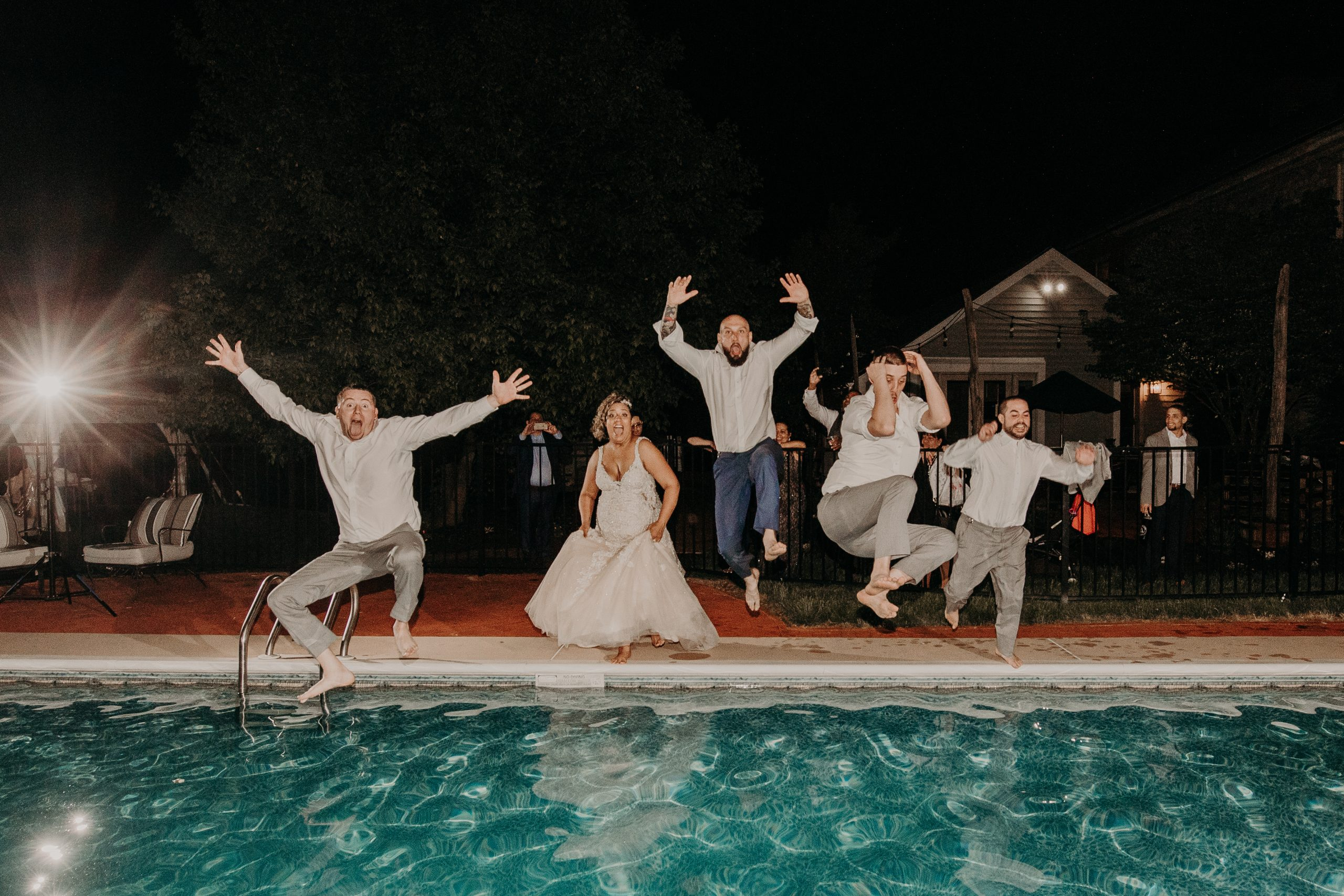 The bride and groom take a dive. Christine and Richard wed on the Chestnut Hill Villa grounds on May of 2019. Captured by Garnet Dahlia Photography and featured on Dream Weddings.