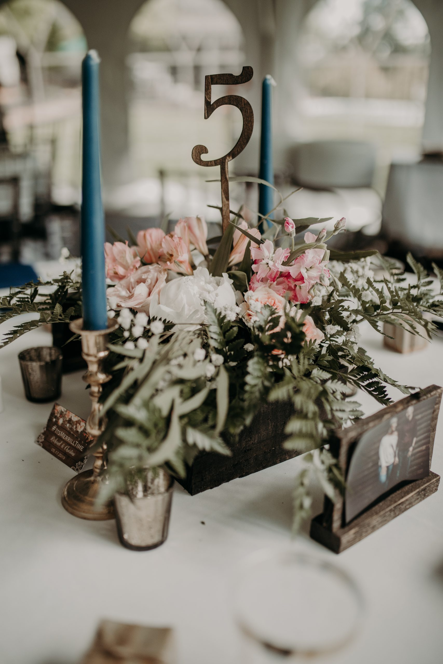Centerpieces to each table varied, which added texture and dimension. Tapered blue candles with table numbers and florals kept your eyes on the reason for the day. Christine and Richard wed on the Chestnut Hill Villa grounds on May of 2019. This organic ethereal styled wedding was captured by Garnet Dahlia Photography and featured on Dream Weddings.
