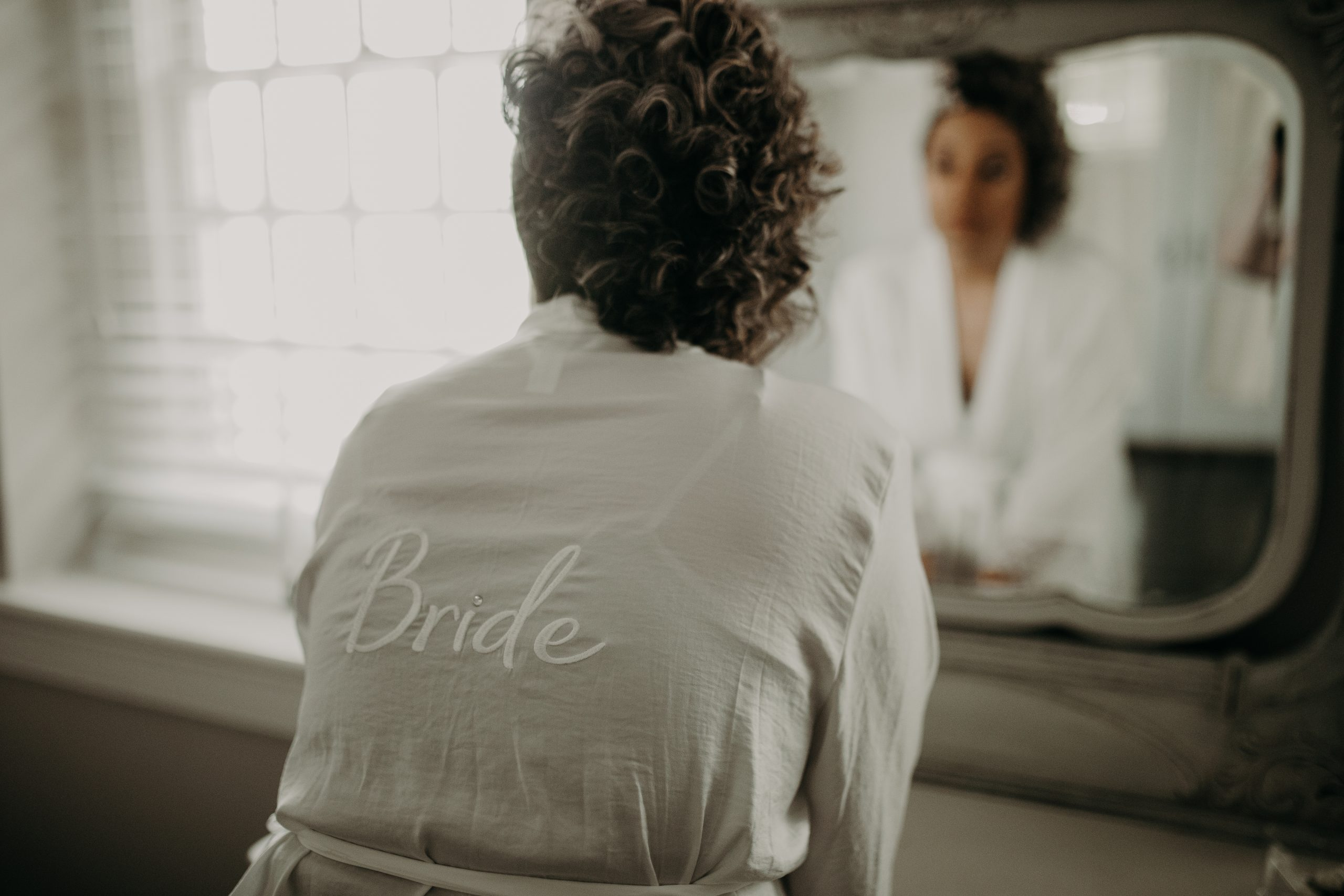 Taking one last look in the mirror before the glam team takes over. Sporting a robe with 'Bride' on the back, there is no confusing who this special day belongs to. Christine and Richard wed on the Chestnut Hill Villa grounds on May of 2019. This organic ethereal styled wedding was captured by Garnet Dahlia Photography and featured on Dream Weddings.