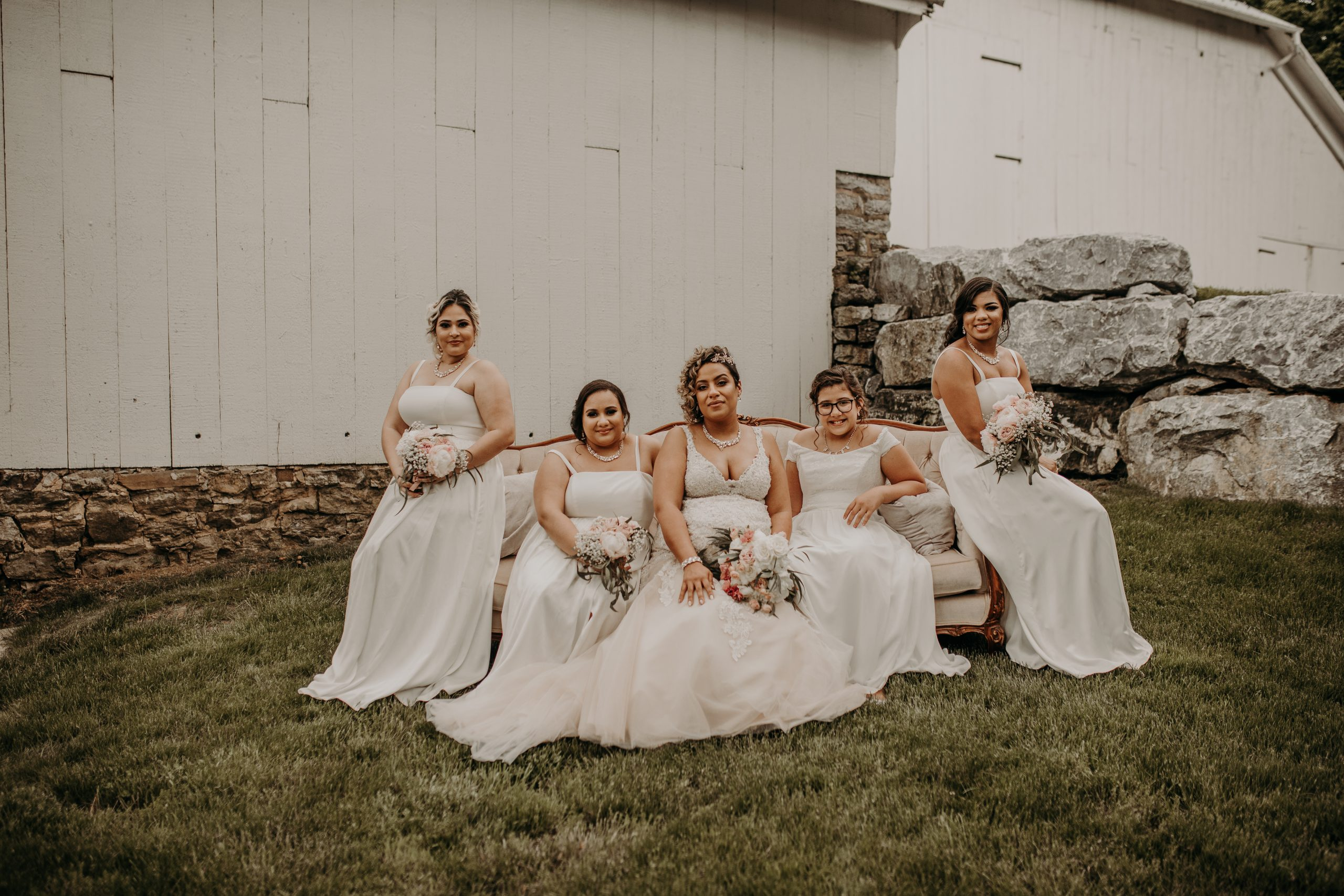 The bridal party is poised and all in white. Christine and Richard wed on the Chestnut Hill Villa grounds on May of 2019. This organic ethereal styled wedding was captured by Garnet Dahlia Photography and featured on Dream Weddings.