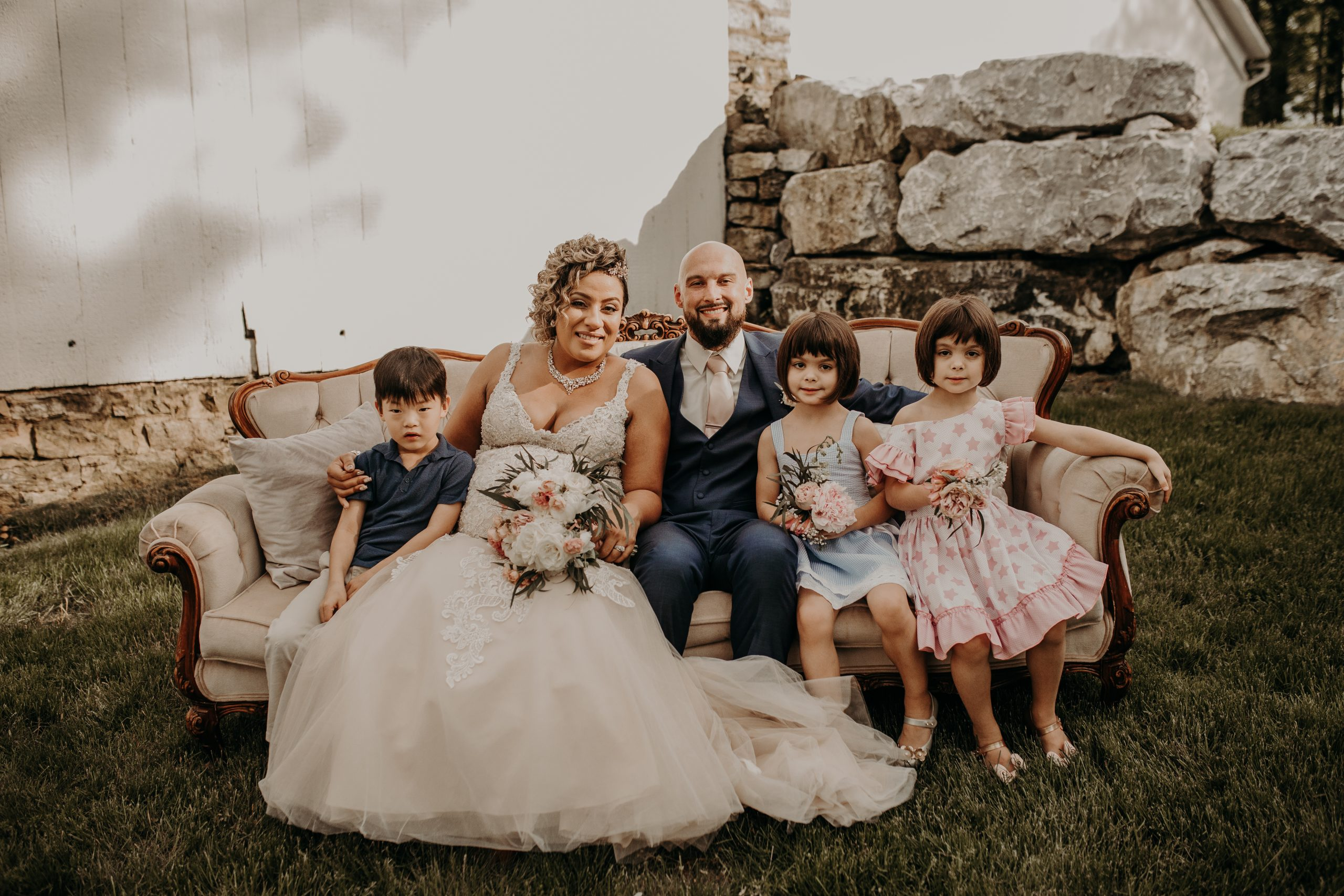 Nieces and nephews sit around their aunt and uncle who just tied the knot! Christine and Richard wed on the Chestnut Hill Villa grounds on May of 2019. This organic ethereal styled wedding was captured by Garnet Dahlia Photography and featured on Dream Weddings.