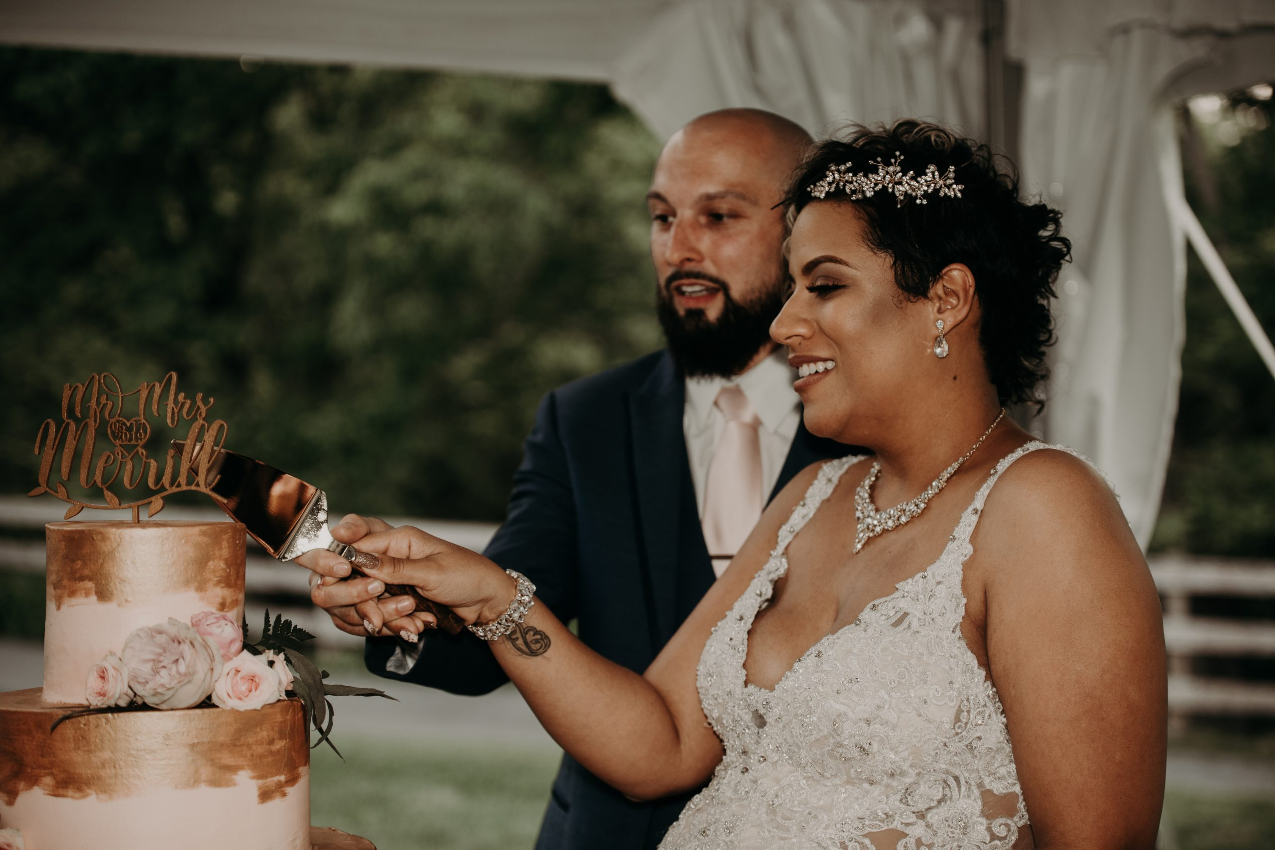 Cutting into their blush pink cake with gold paint accents. Christine and Richard wed on the Chestnut Hill Villa grounds on May of 2019. This organic ethereal styled wedding was captured by Garnet Dahlia Photography and featured on Dream Weddings.