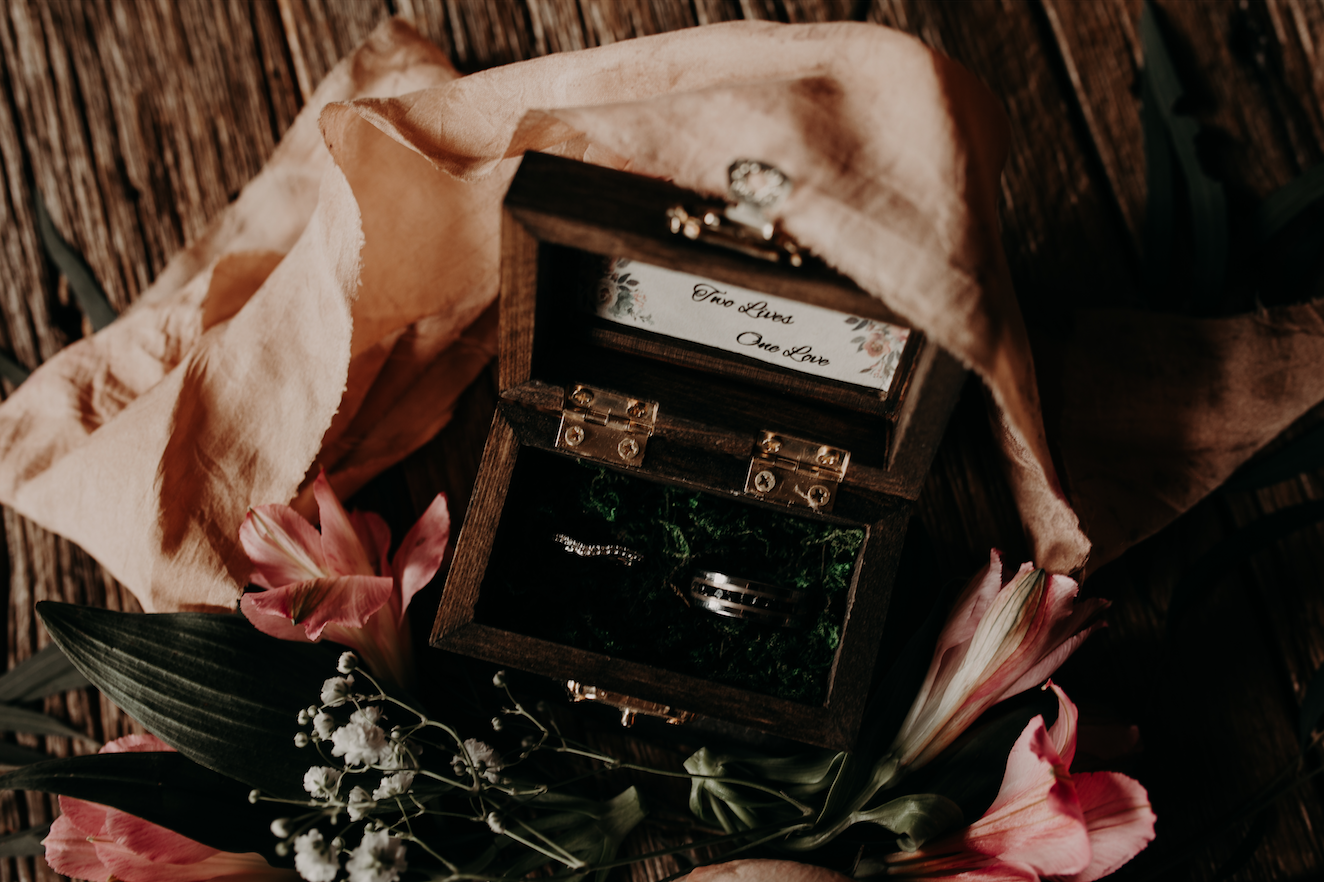 A wooden box holds the wedding rings of the couple. Bedded in a green velvet, the couple tied in their theme perfectly. Christine and Richard wed on the Chestnut Hill Villa grounds on May of 2019. This organic ethereal styled wedding was captured by Garnet Dahlia Photography and featured on Dream Weddings.
