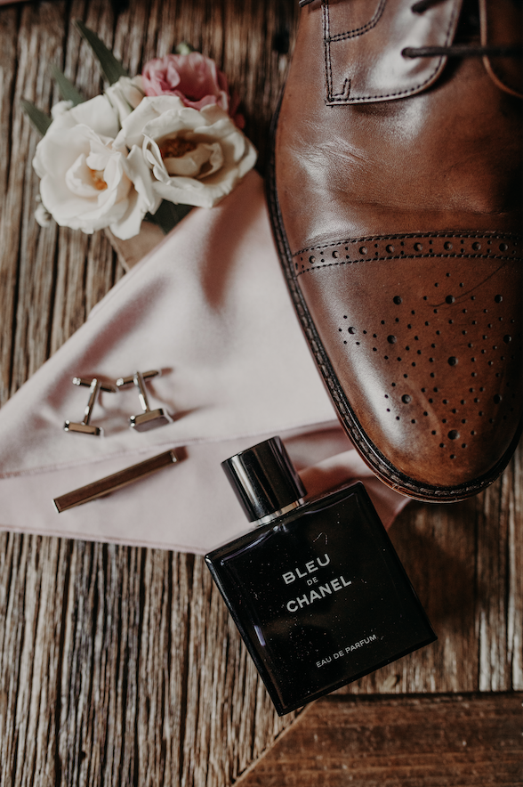 Details of the grooms attire include that of Bleu Chanel cologne, silver cufflinks, and a deep brown shoe. Christine and Richard wed on the Chestnut Hill Villa grounds on May of 2019. This organic ethereal styled wedding was captured by Garnet Dahlia Photography and featured on Dream Weddings.