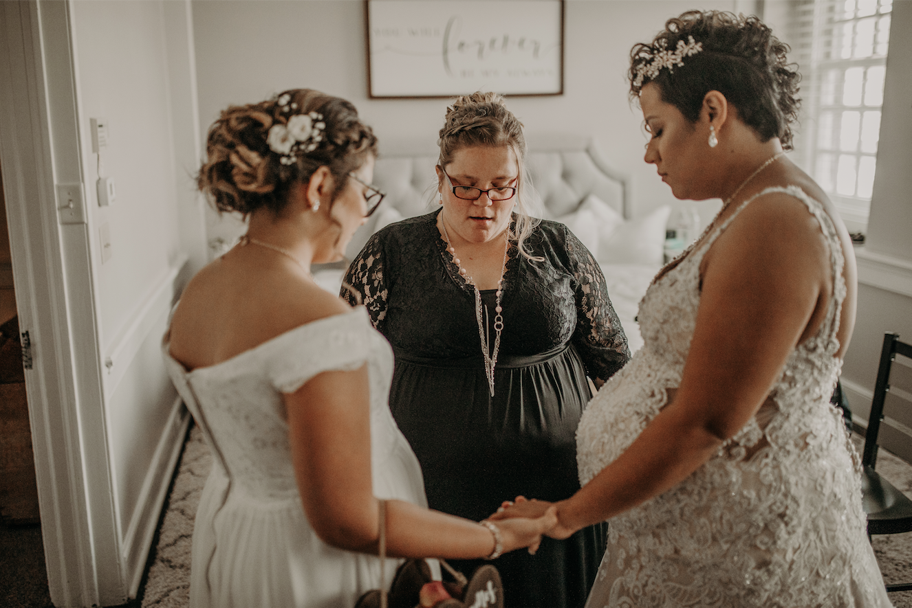 the officiant, bride and daughter of the bride hold hands in prayer before the ceremony. Christine and Richard wed on the Chestnut Hill Villa grounds on May of 2019. This organic ethereal styled wedding was captured by Garnet Dahlia Photography and featured on Dream Weddings.
