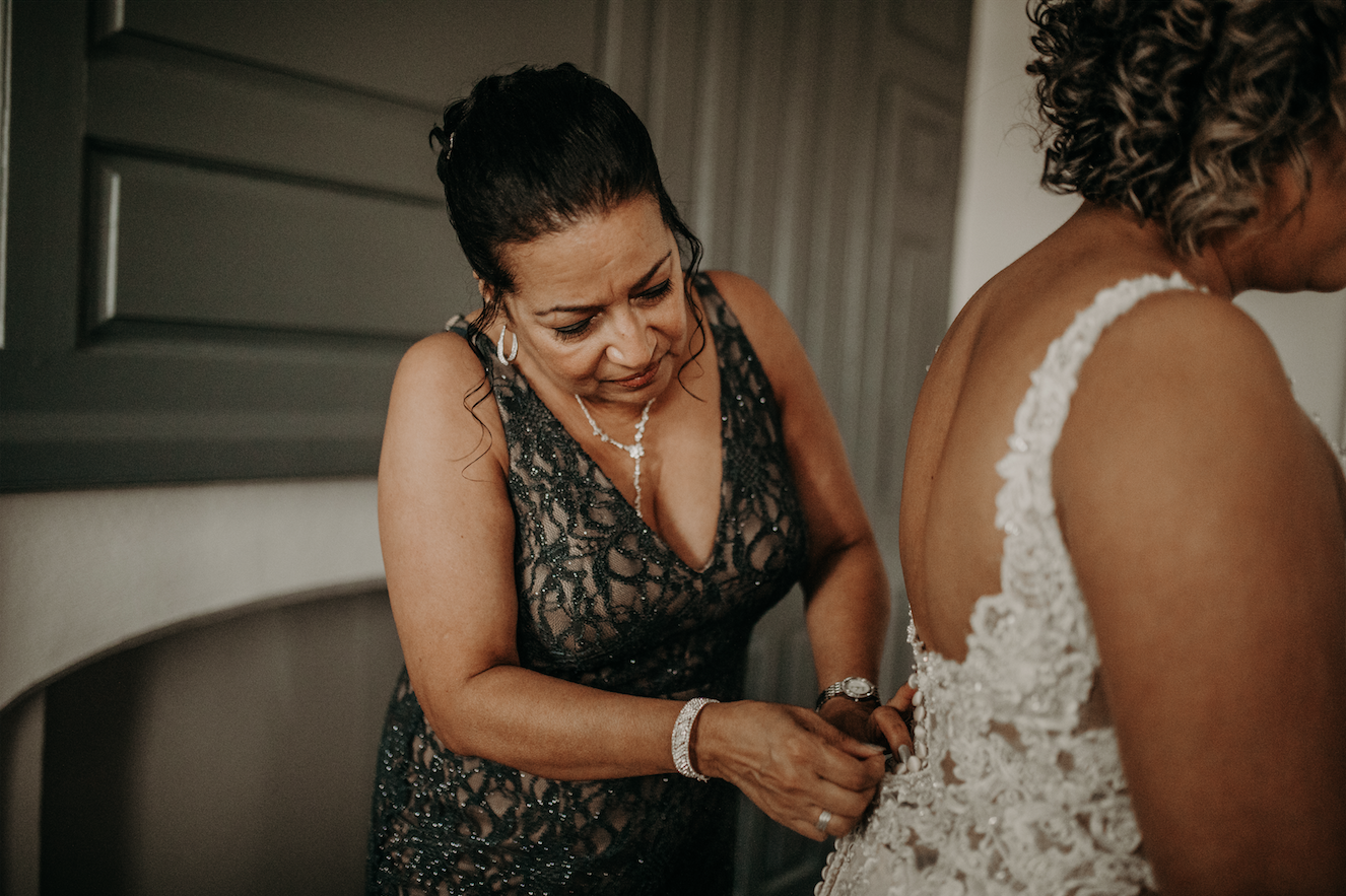 The brides mother helps to make sure every button is done before she walks down the isle. A dark, plunging neckline for the mother of the bride sets the tone. Christine and Richard wed on the Chestnut Hill Villa grounds on May of 2019. This organic ethereal styled wedding was captured by Garnet Dahlia Photography and featured on Dream Weddings.