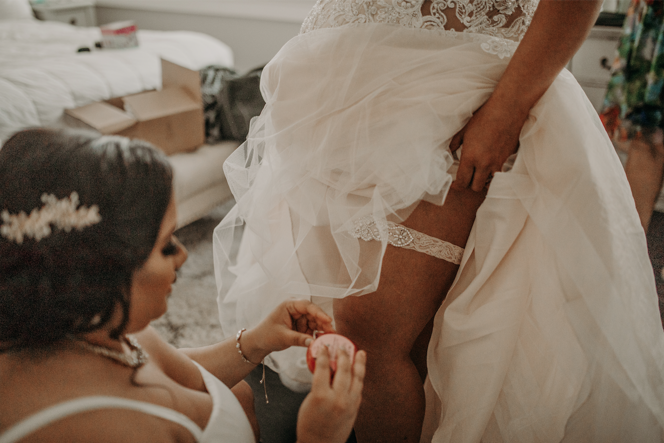 Putting on the garder requires some help. With silver accented jewels and a classic white fabric, the bride is good to go. Christine and Richard wed on the Chestnut Hill Villa grounds on May of 2019. This organic ethereal styled wedding was captured by Garnet Dahlia Photography and featured on Dream Weddings.