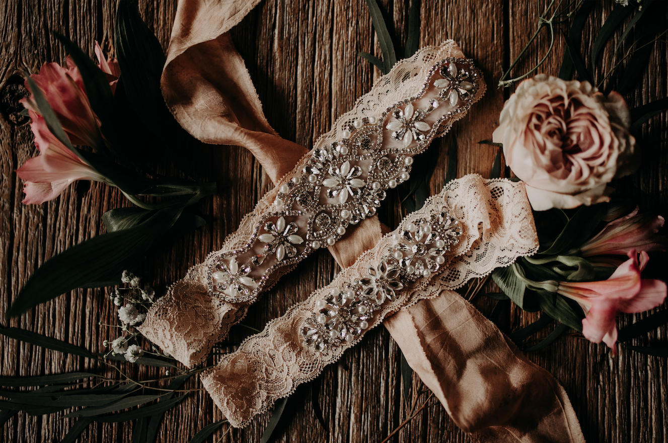 Blush pink garters decked out in silver accents is the perfect personal touch to any wedding attire. Christine and Richard wed on the Chestnut Hill Villa grounds on May of 2019. This organic ethereal styled wedding was captured by Garnet Dahlia Photography and featured on Dream Weddings.