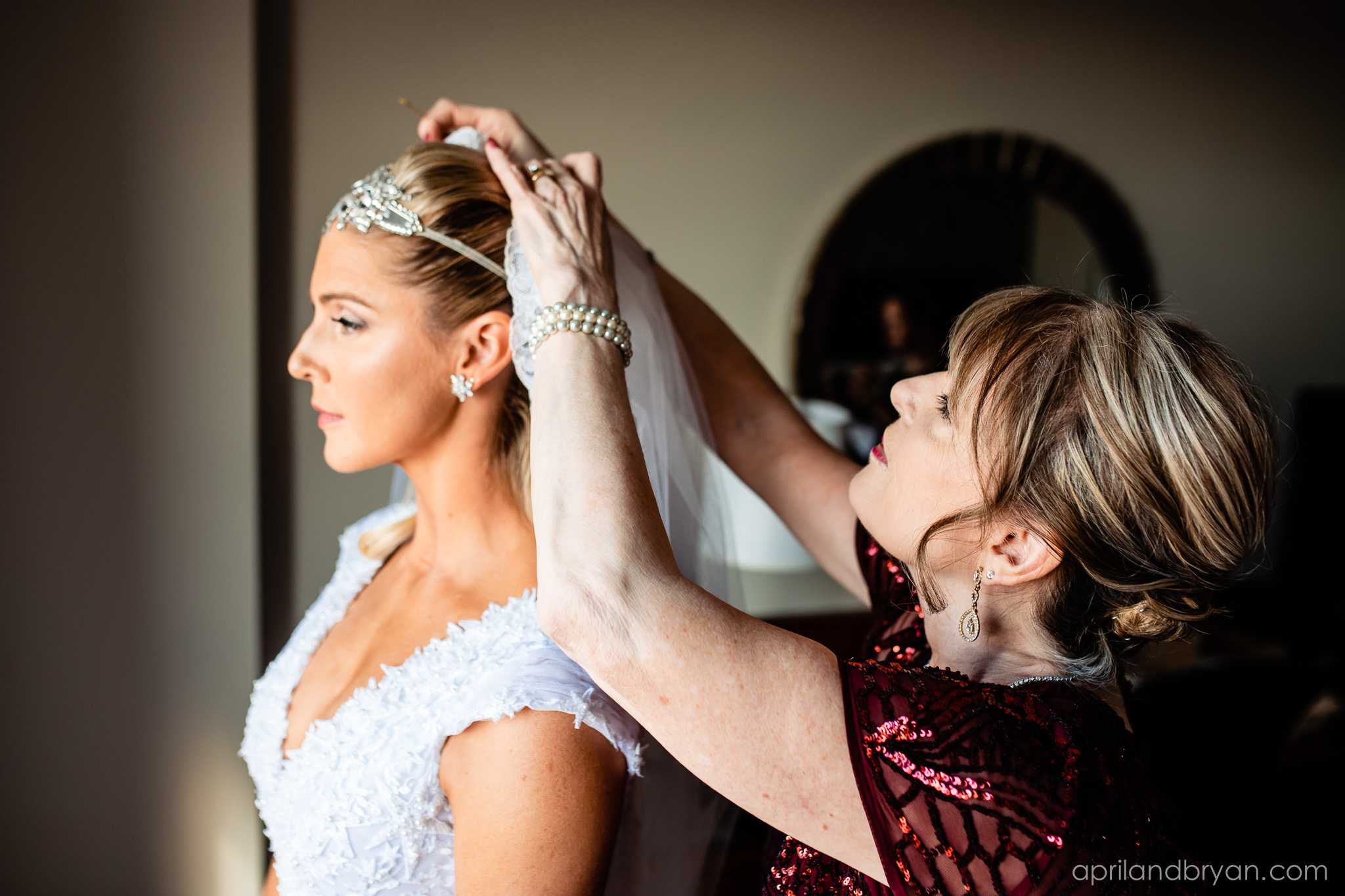 The final touches while putting on the veil have arrived. Nicholas and Rebecca Fasnacht tie the not at Tellus360 on November 1, 2019. Captured by April & Bryan Photography and featured on Dream Weddings.