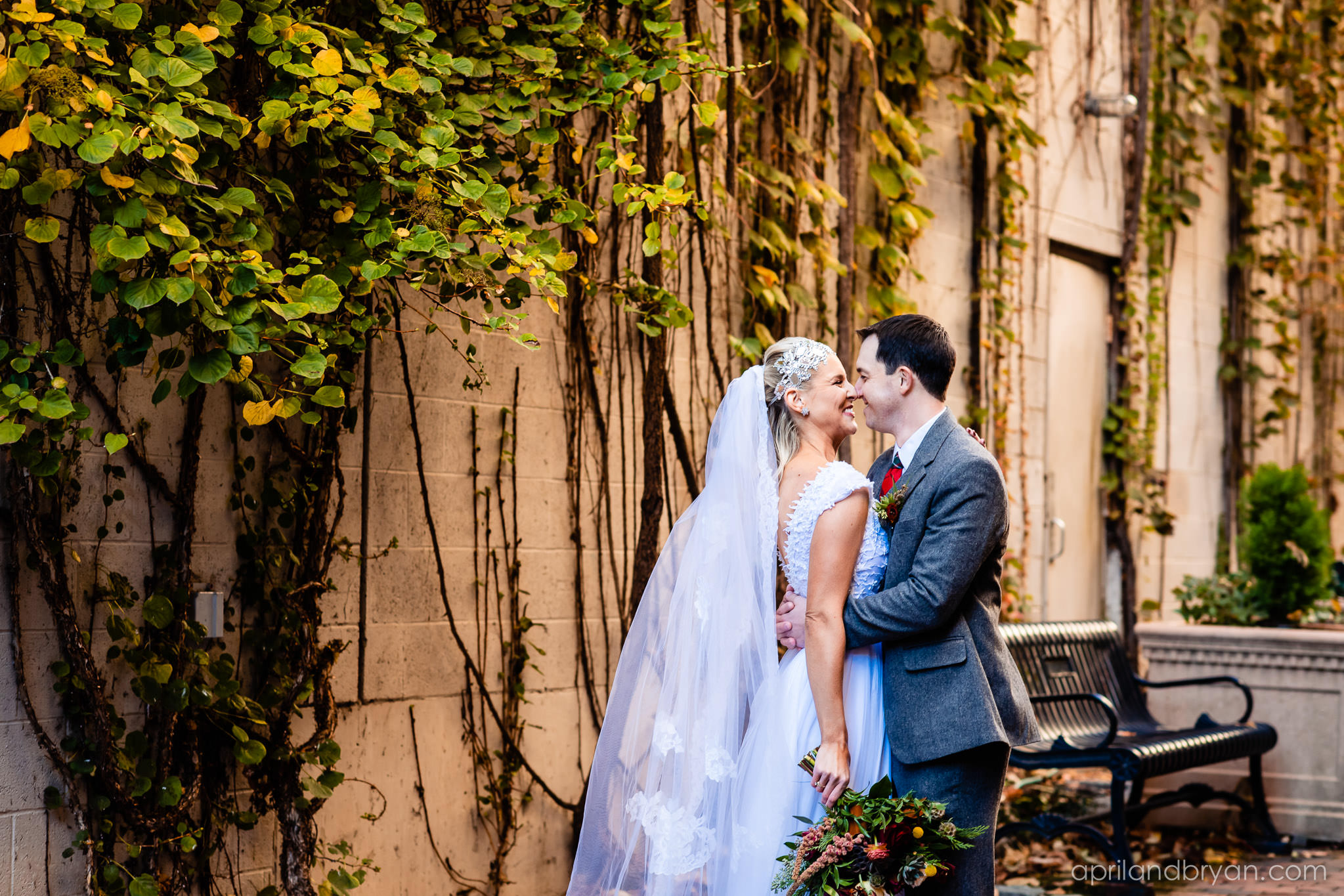 Bride and groom embrace each other before they walk down the isle. The pure white dress contratss the groom's rey blazer. Nicholas and Rebecca Fasnacht tie the not at Tellus360 on November 1, 2019. Captured by April & Bryan Photography and featured on Dream Weddings.