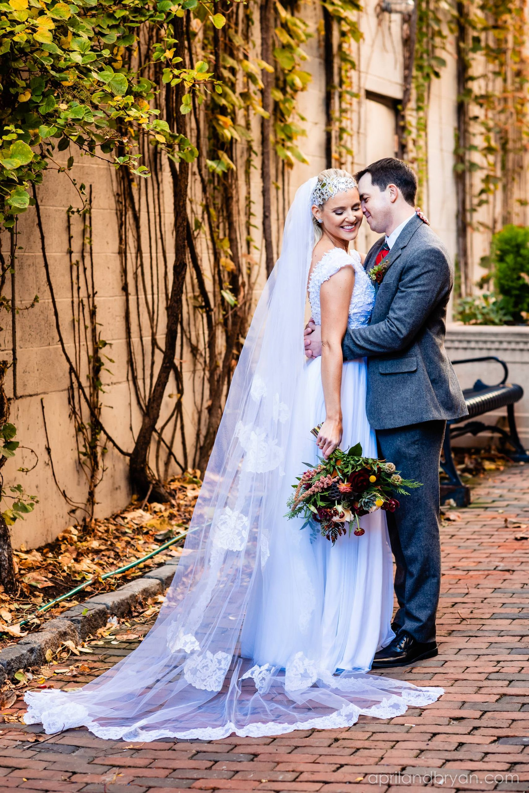 the two engage in a lover embrace with a pure white gown and succulents detailing her bouquet. Nicholas and Rebecca Fasnacht tie the not at Tellus360 on November 1, 2019. Captured by April & Bryan Photography and featured on Dream Weddings.