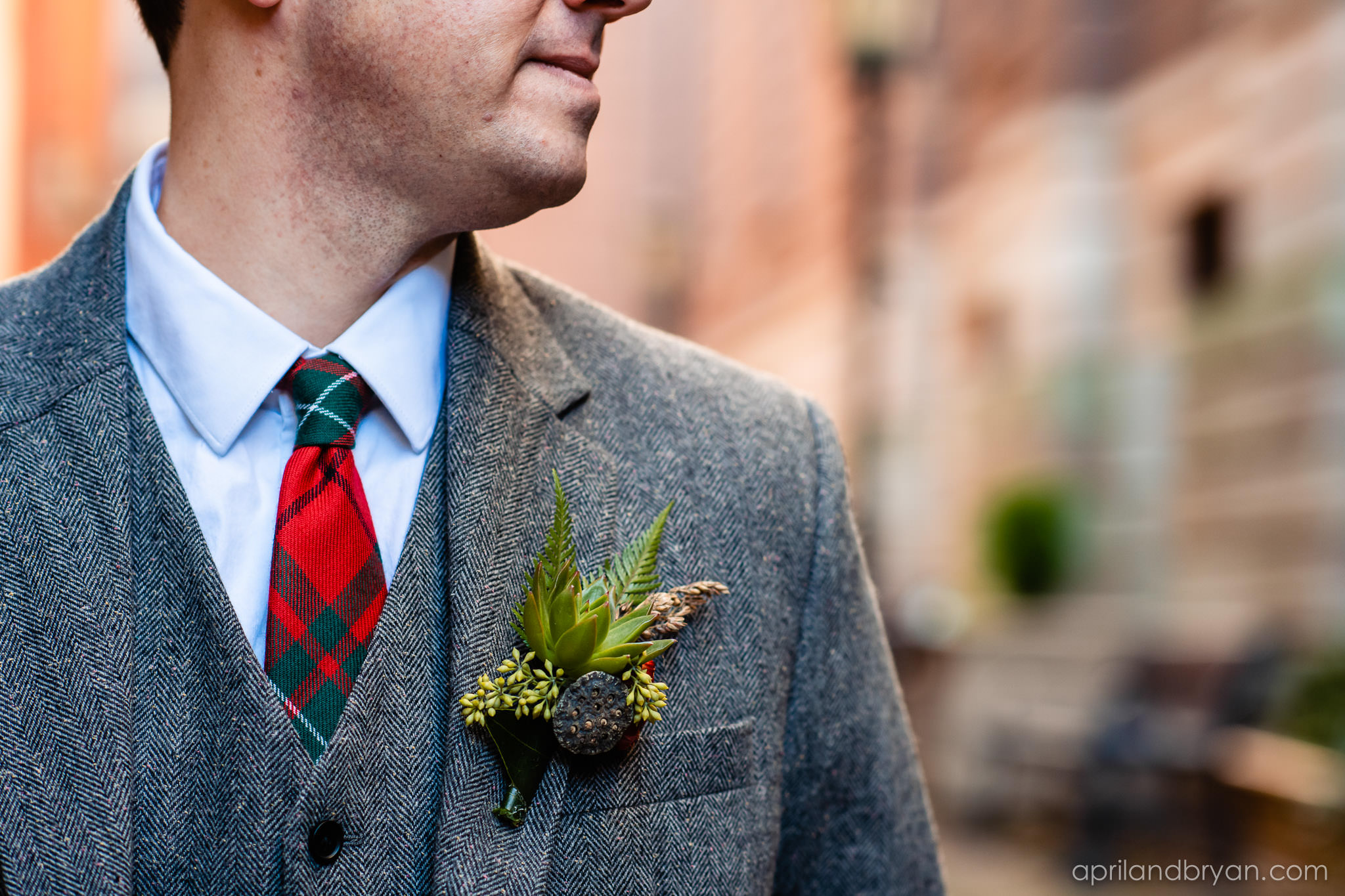 A succulent in his boutonniere and plaid to offset this Irish wedding. Nicholas and Rebecca Fasnacht tie the not at Tellus360 on November 1, 2019. Captured by April & Bryan Photography and featured on Dream Weddings.