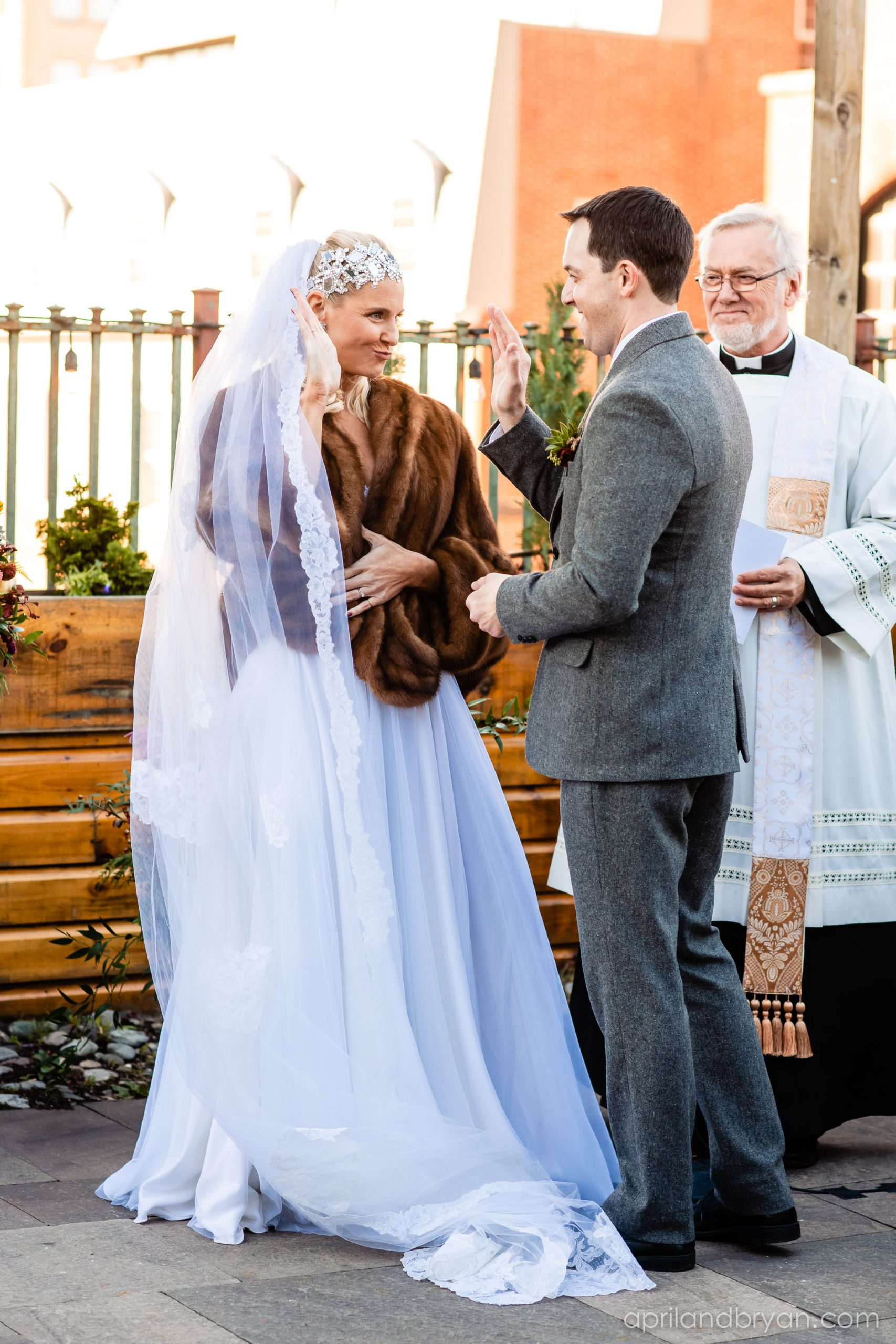 High-fiving each other as they prepare to walk back down the isle as husband and wife. Nicholas and Rebecca Fasnacht tie the not at Tellus360 on November 1, 2019. Captured by April & Bryan Photography and featured on Dream Weddings.