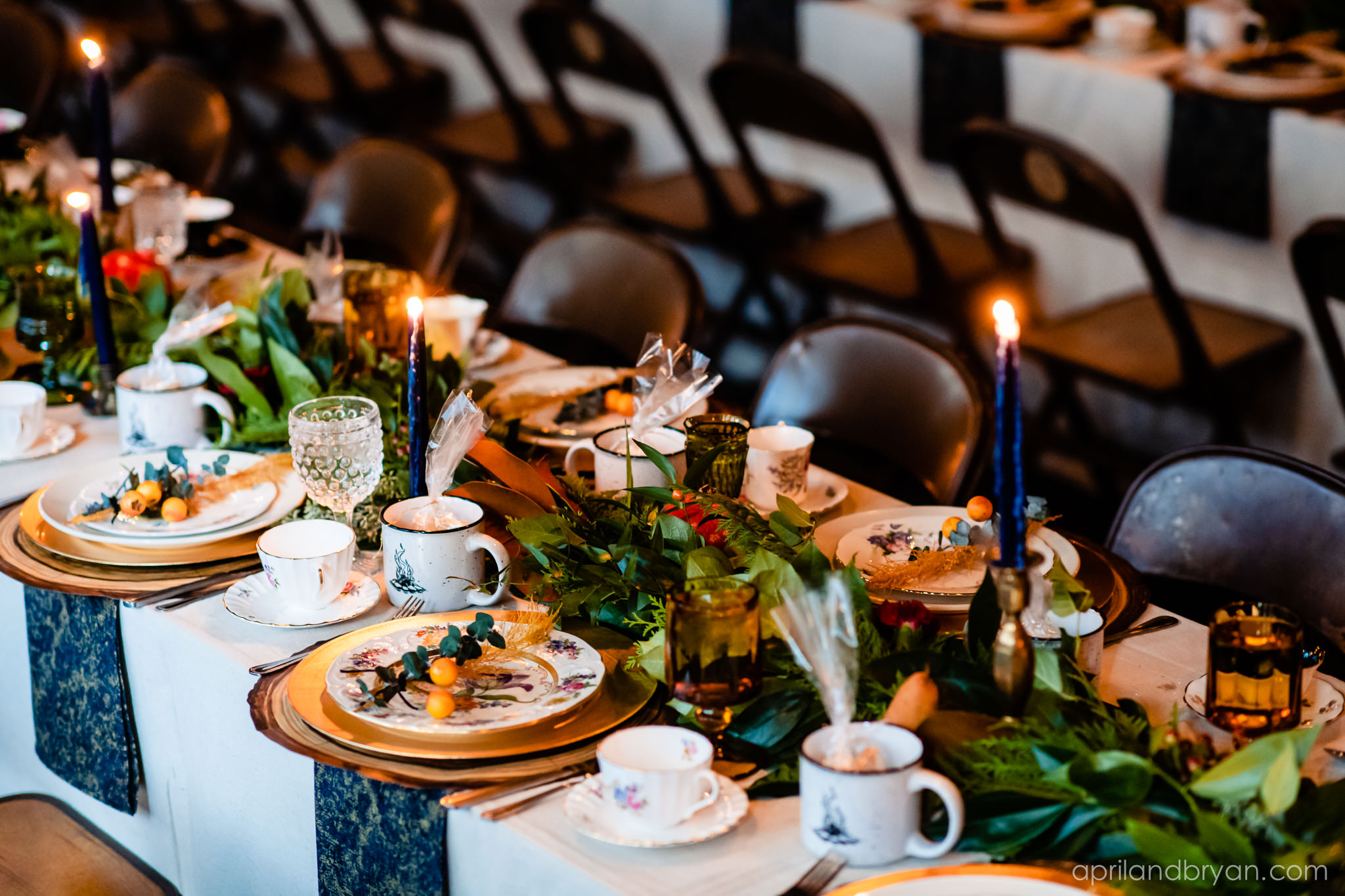 greenery lined the table like an organic table runner. Nicholas and Rebecca Fasnacht tie the not at Tellus360 on November 1, 2019. Captured by April & Bryan Photography and featured on Dream Weddings.