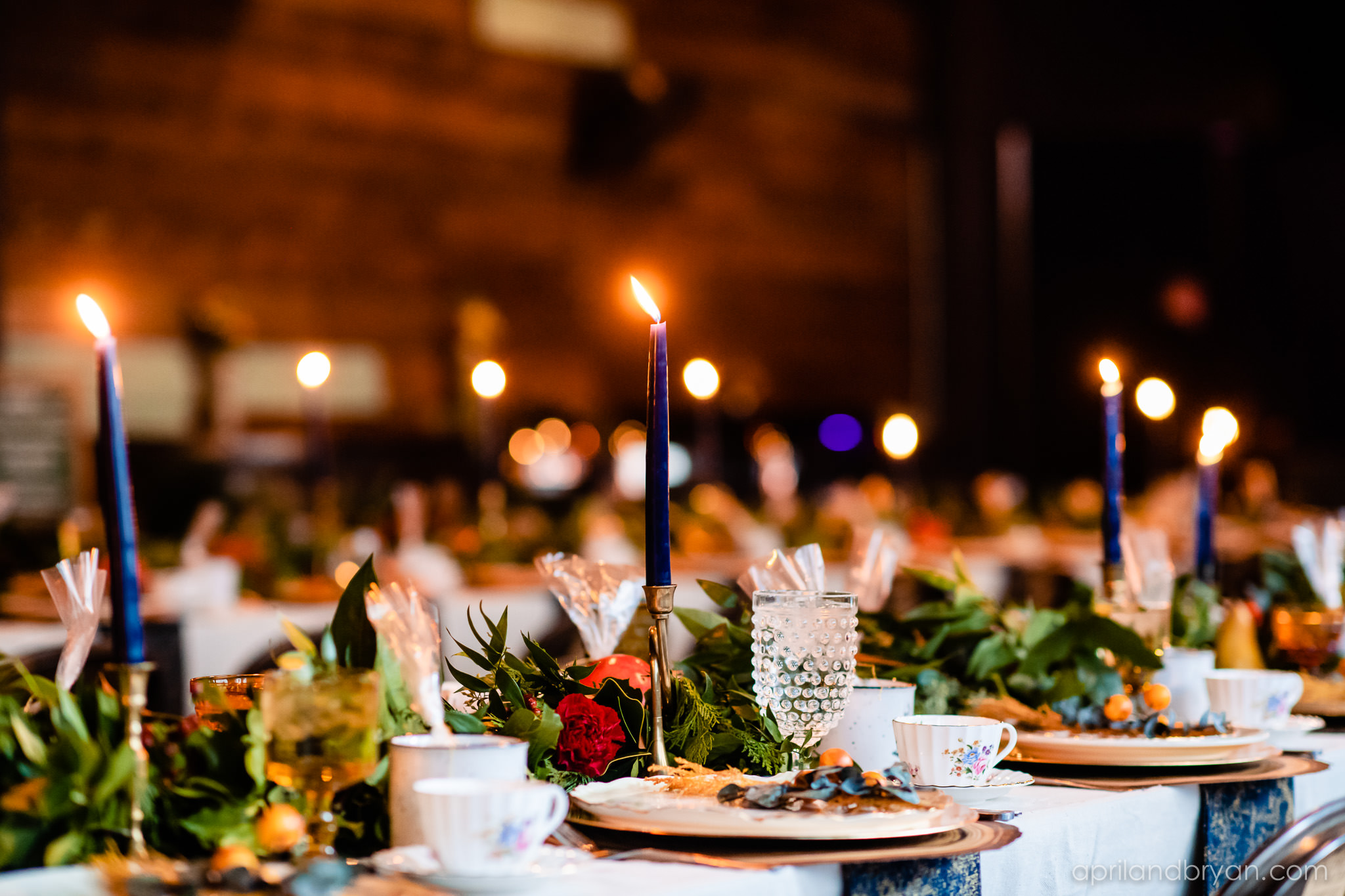 The tablescape was riddled with greenery, navy tapered candles, goblets, gold trimmed tea cups and extravagant gold plates. Nicholas and Rebecca Fasnacht tie the not at Tellus360 on November 1, 2019. Captured by April & Bryan Photography and featured on Dream Weddings.