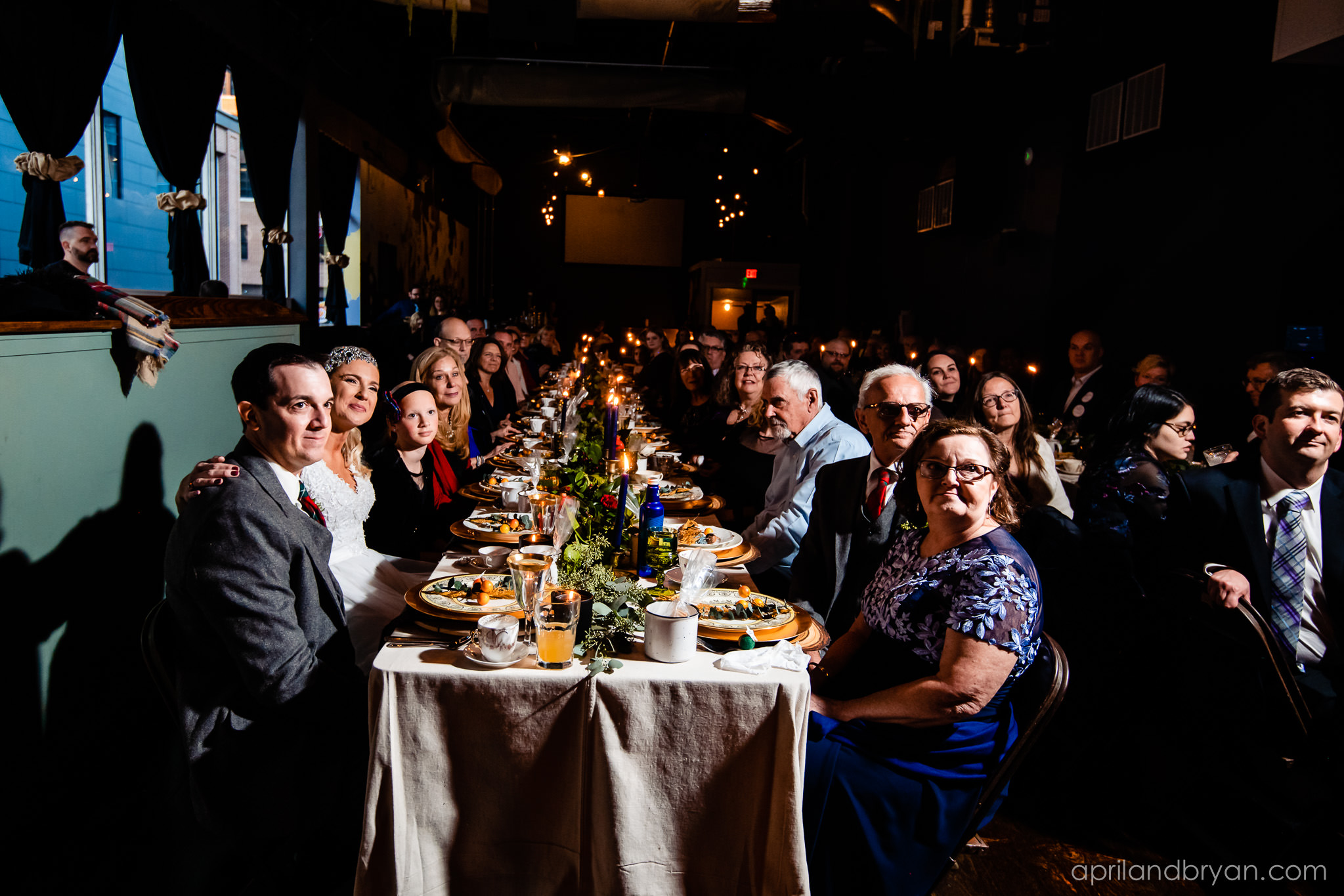 Huge king tables seat the guests at the wedding and for the most part is only lit by candle light. Nicholas and Rebecca Fasnacht tie the not at Tellus360 on November 1, 2019. Captured by April & Bryan Photography and featured on Dream Weddings.