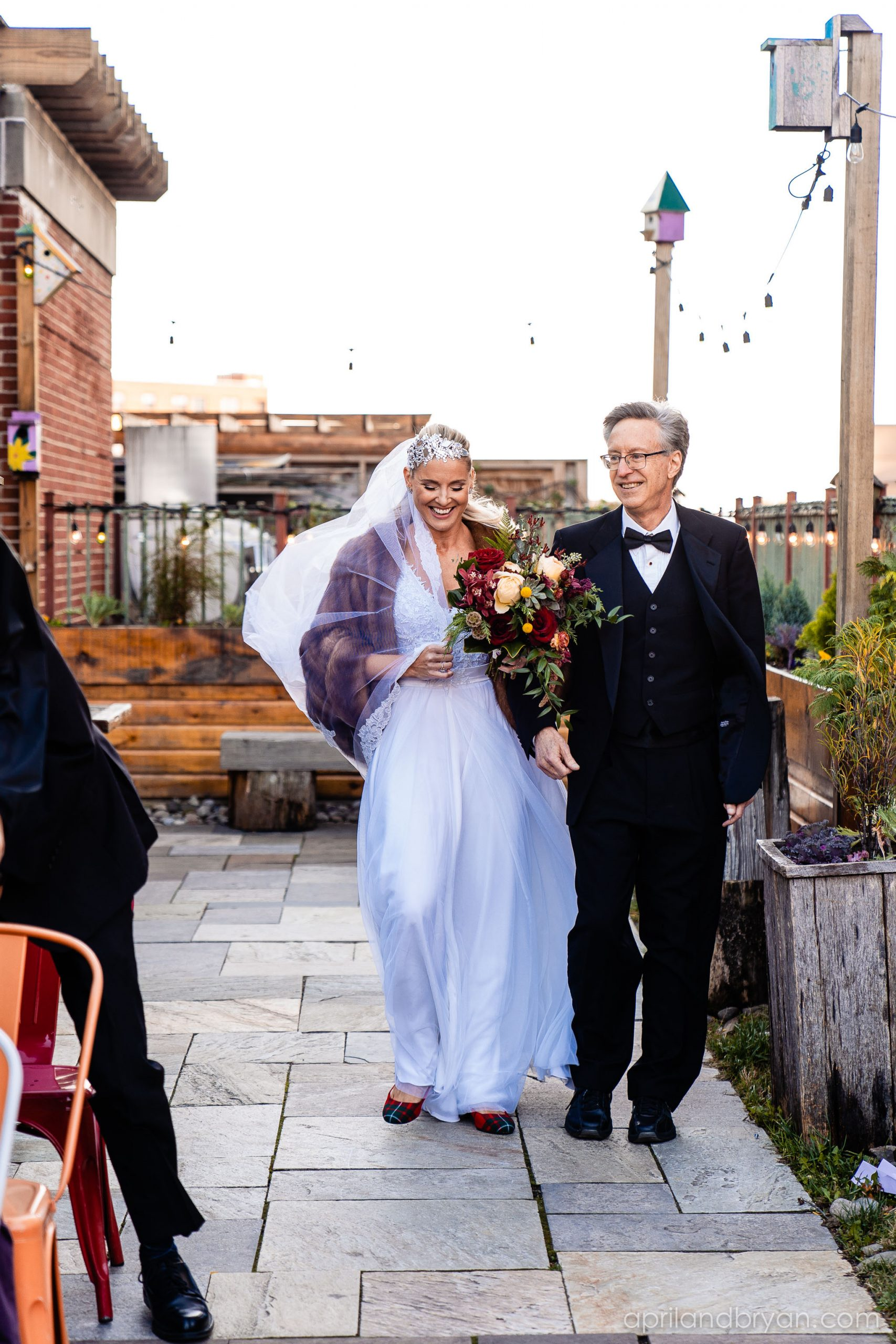 Father of the bride walks her down the isle in plaid flats and a fur shaw. Nicholas and Rebecca Fasnacht tie the not at Tellus360 on November 1, 2019. Captured by April & Bryan Photography and featured on Dream Weddings.