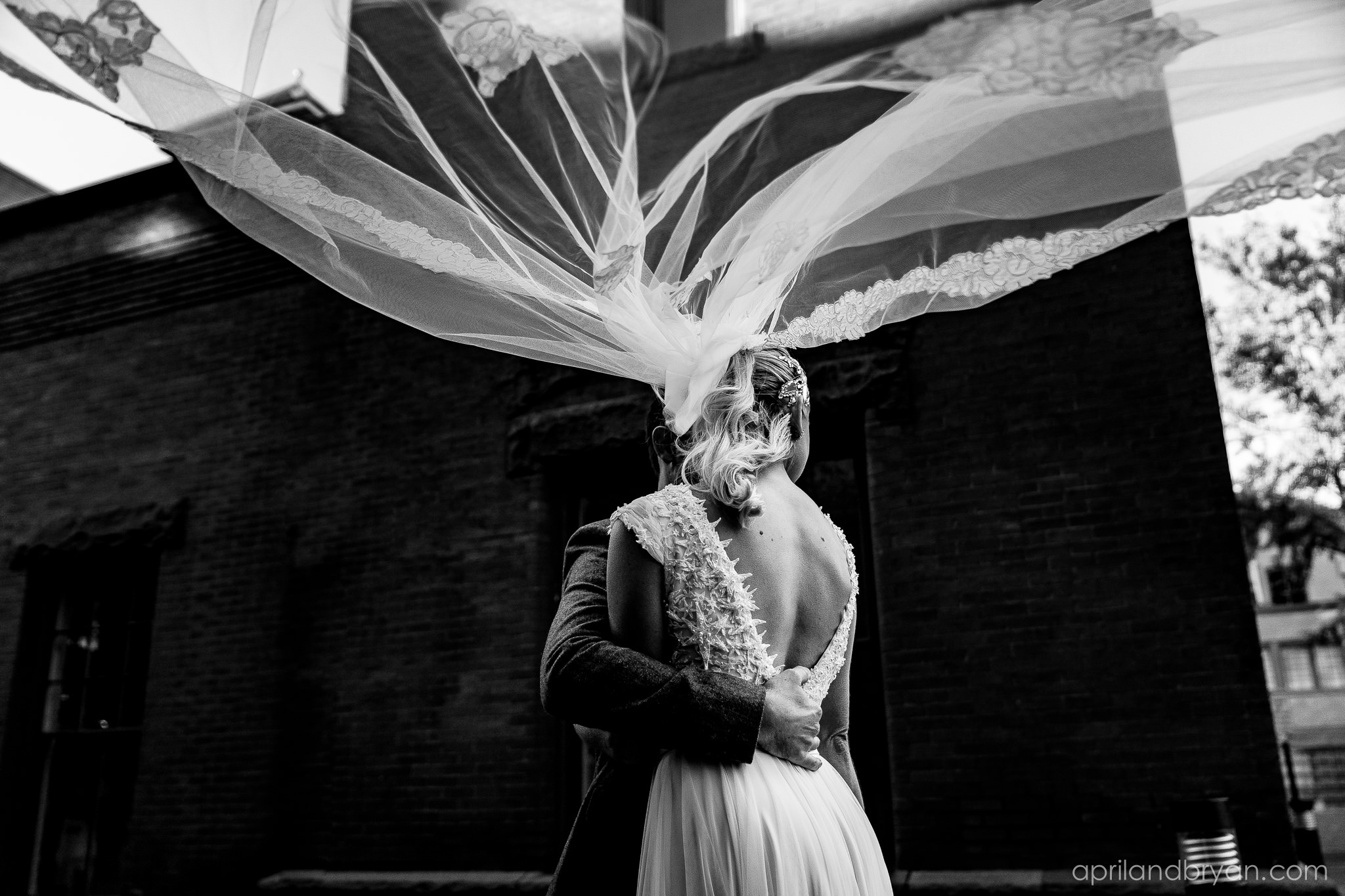 A classically romantic photo of the bride and groom. Nicholas and Rebecca Fasnacht tie the not at Tellus360 on November 1, 2019. Captured by April & Bryan Photography and featured on Dream Weddings.