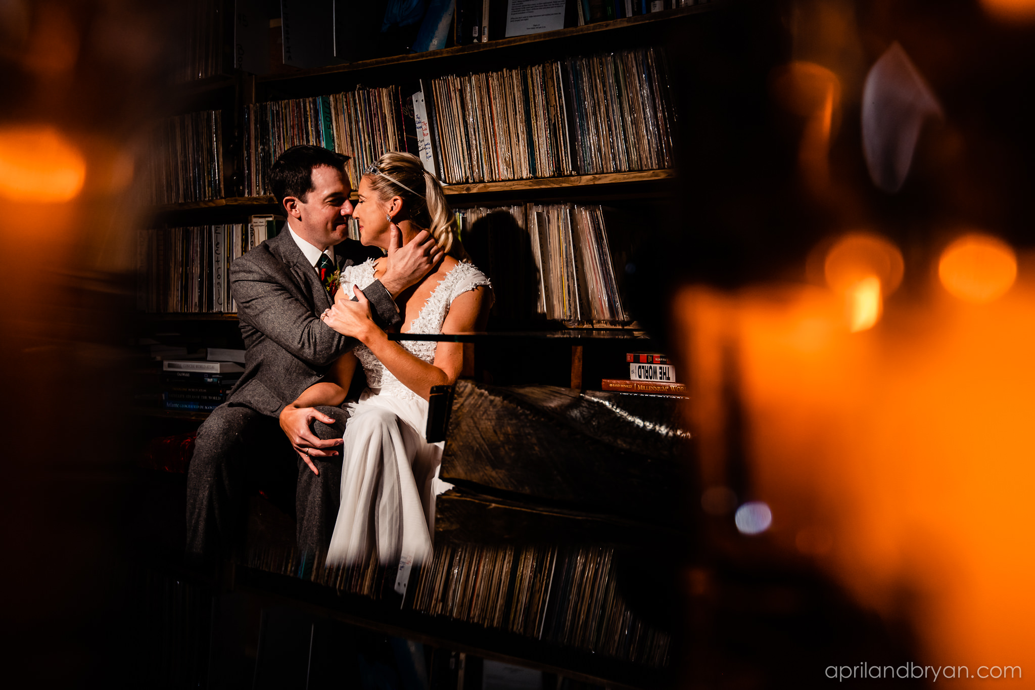 The couple sneak away for a chance to tae some photos by the albums exhibited at the venue. Nicholas and Rebecca Fasnacht tie the not at Tellus360 on November 1, 2019. Captured by April & Bryan Photography and featured on Dream Weddings.