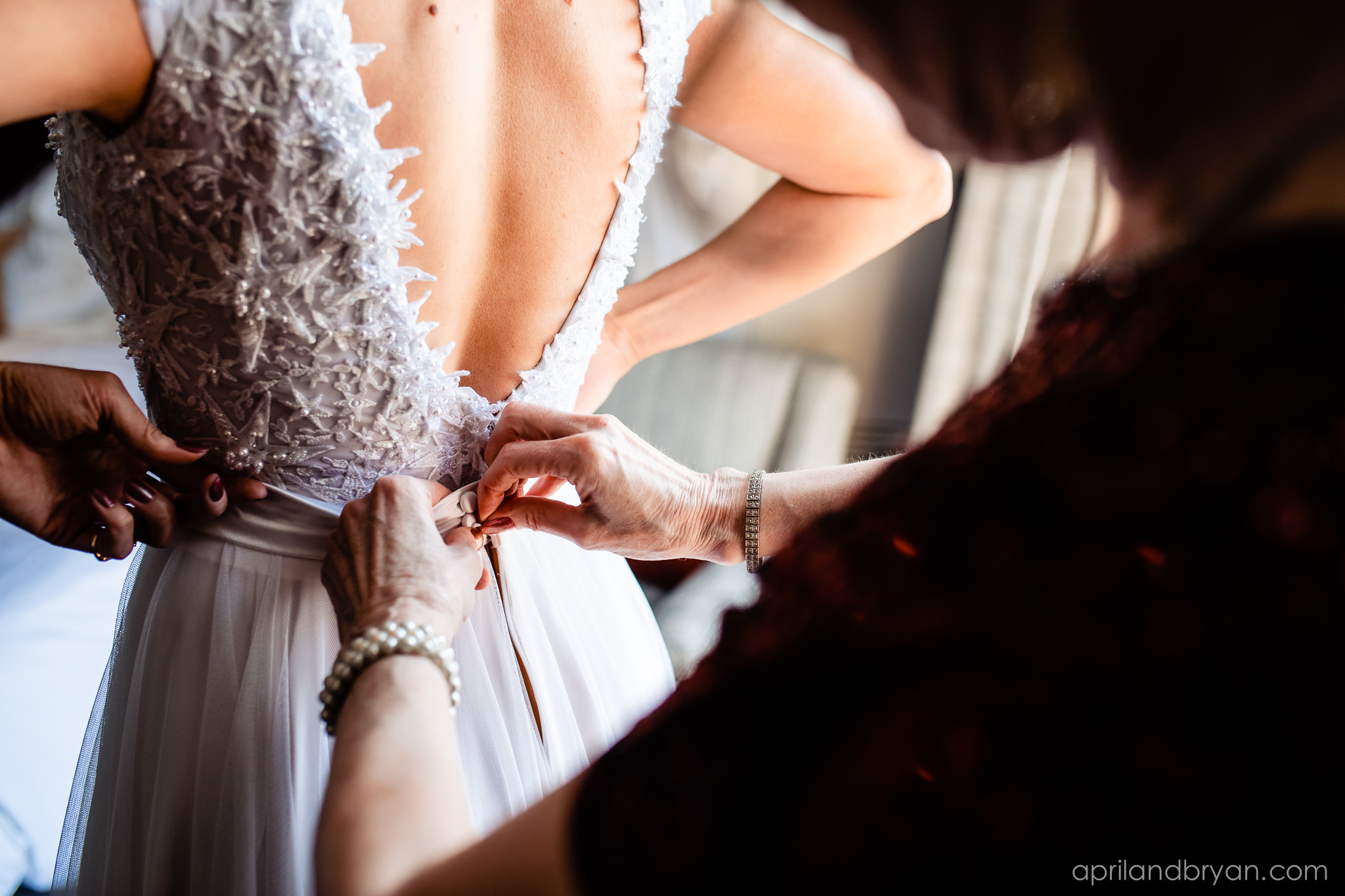 Zipping up the a-line dress and clasping the last of each snap. Nicholas and Rebecca Fasnacht tie the not at Tellus360 on November 1, 2019. Captured by April & Bryan Photography and featured on Dream Weddings.