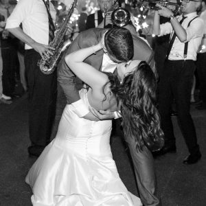 Groom dip kisses his bride on the dance floor