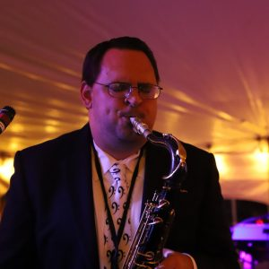 A man wearing glasses and a suit plays the saxophone on stage