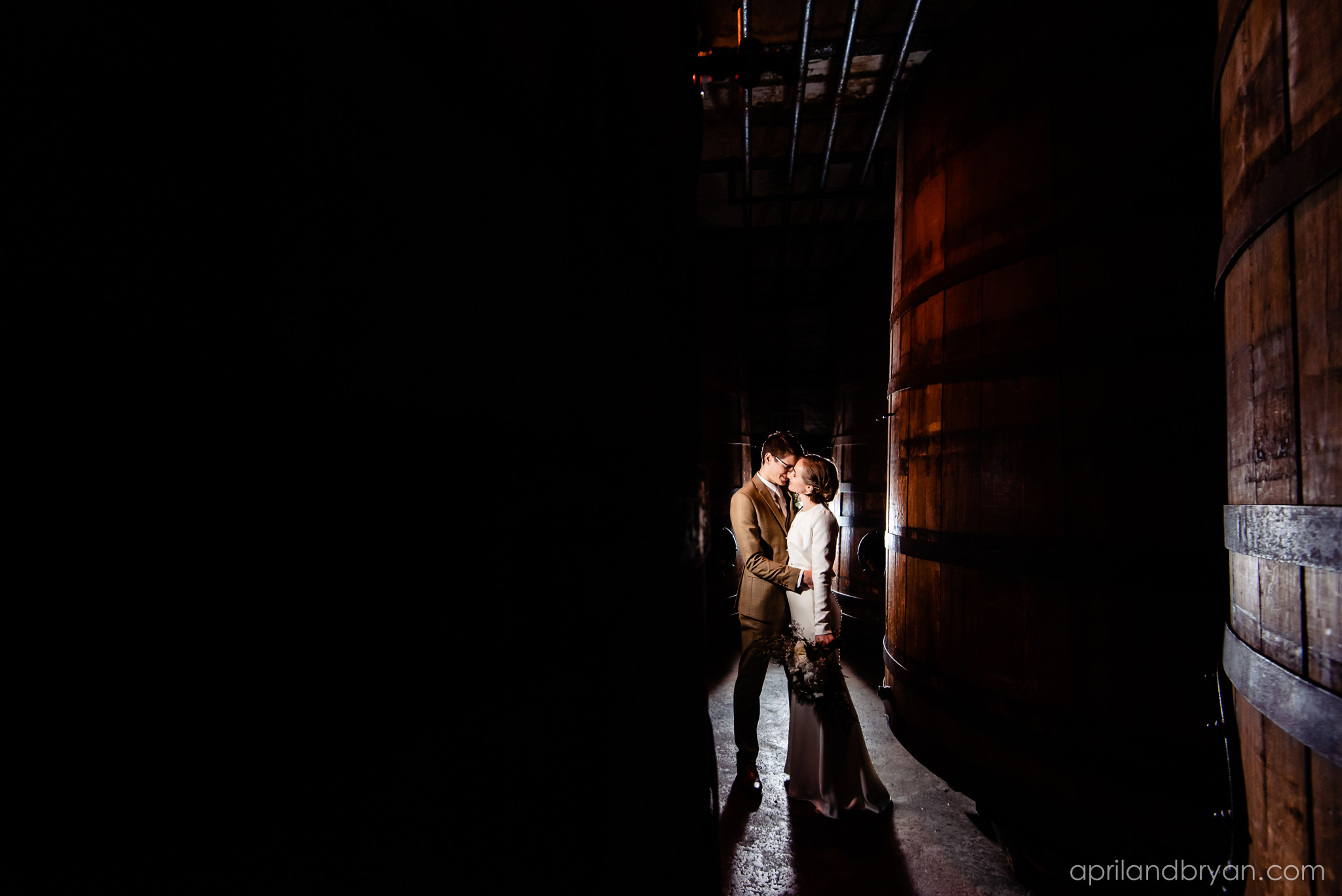 Sneaking away to the aging barrels, the newlyweds steal a kiss. Hannah and Ethan Farrell had their classic romantic styled wedding held at their home in Mount Joy, followed by a reception at the catacombs underneath Bube's Brewery. Photographed by April & Bryan Photography, the couple had the opportunity to showcase their early 1900s style and accommodate a small guest list. Featured on Dream Weddings.