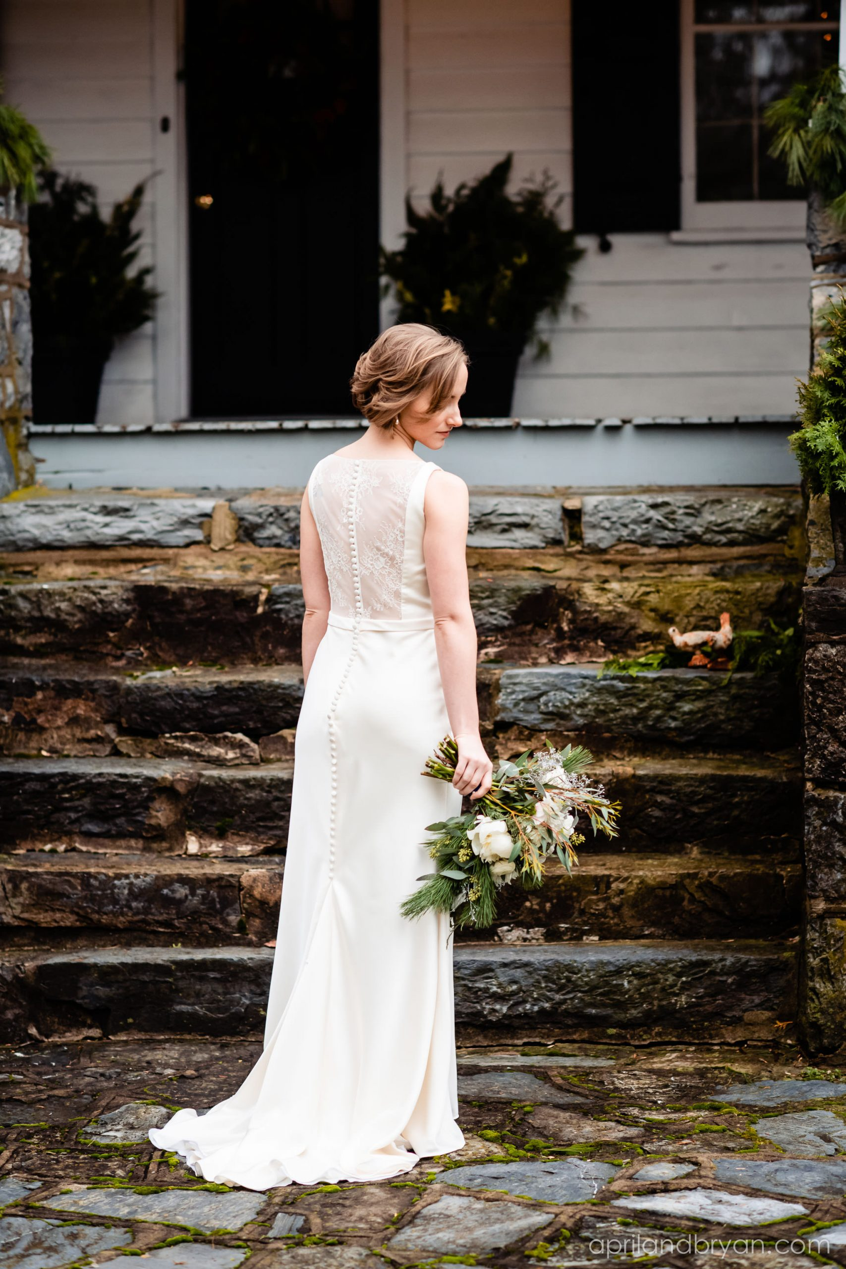 A trail of buttons line the back of Hannah as she takes a moment before she walks down the isle. Hannah and Ethan Farrell had their classic romantic styled wedding held at their home in Mount Joy, followed by a reception at the catacombs underneath Bube's Brewery. Photographed by April & Bryan Photography, the couple had the opportunity to showcase their early 1900s style and accommodate a small guest list. Featured on Dream Weddings.