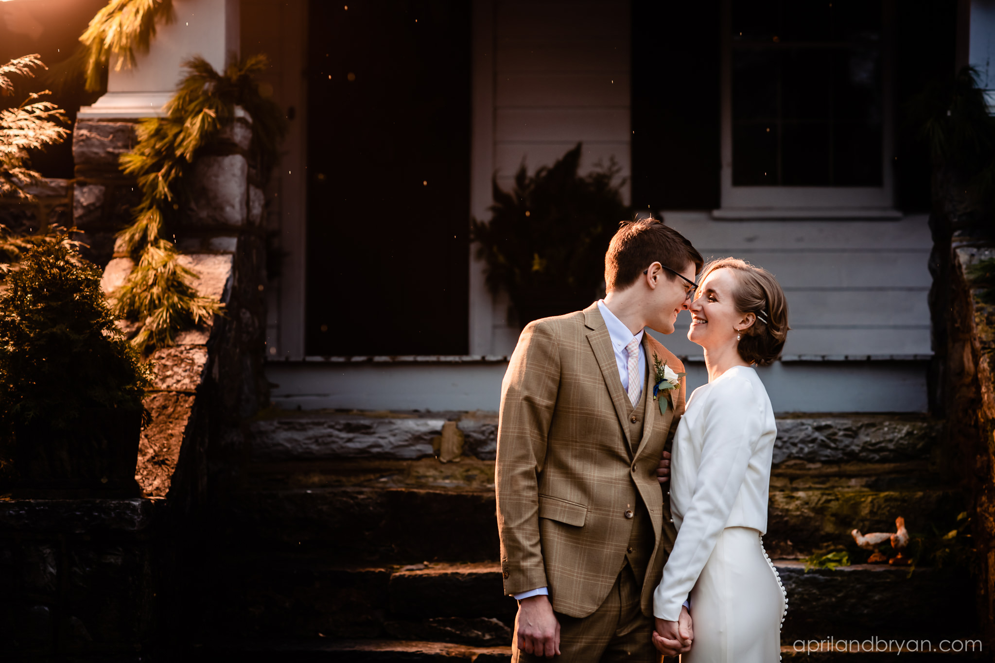 Looking like a couple straight out of the 40s, the two stand in front of their Mount Joy home. Hannah and Ethan Farrell had their classic romantic styled wedding held at their home in Mount Joy, followed by a reception at the catacombs underneath Bube's Brewery. Photographed by April & Bryan Photography, the couple had the opportunity to showcase their early 1900s style and accommodate a small guest list. Featured on Dream Weddings.