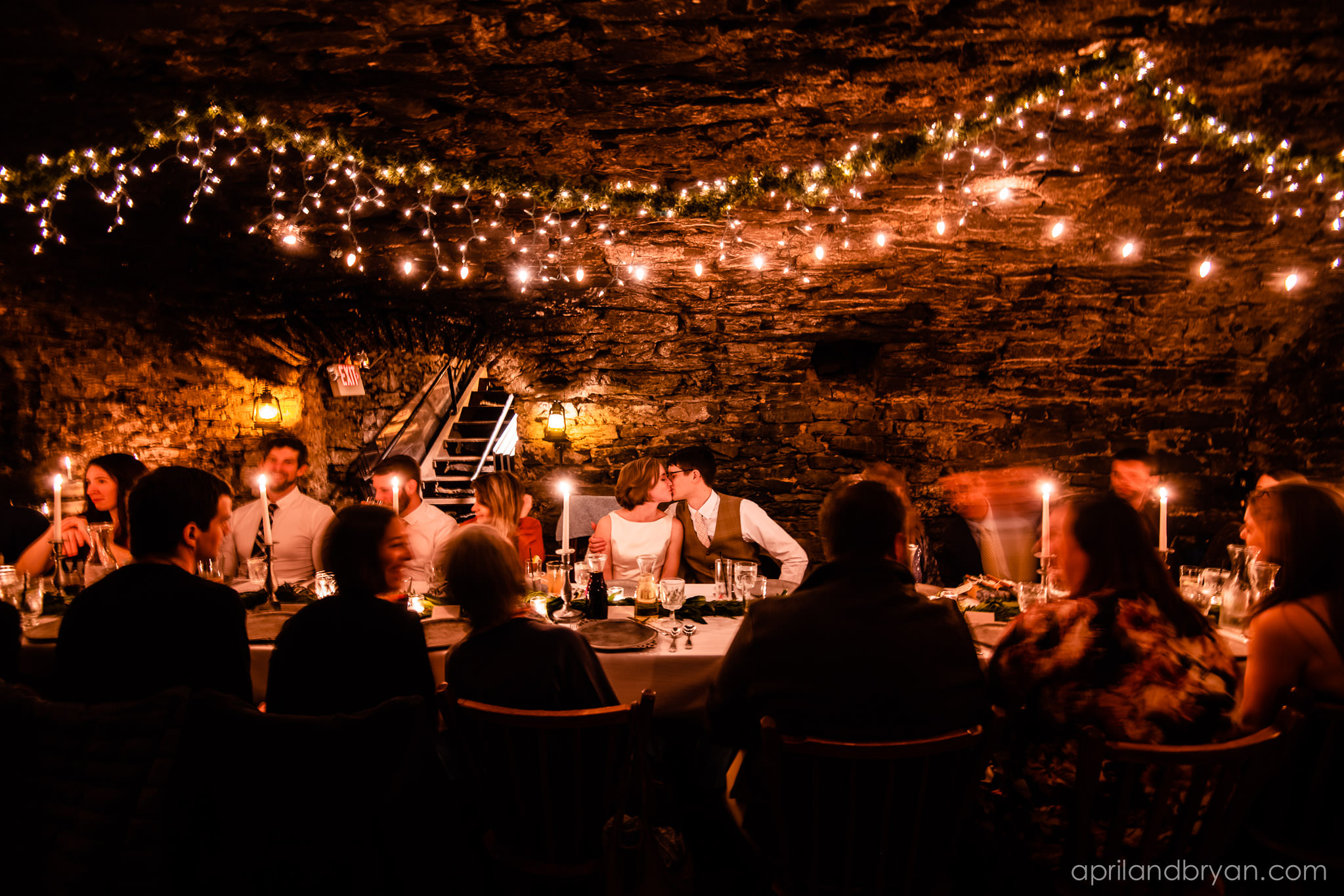 the newly wedded couple share a kiss at their reception location under string lights and a candle lit meal. Hannah and Ethan Farrell had their classic romantic styled wedding held at their home in Mount Joy, followed by a reception at the catacombs underneath Bube's Brewery. Photographed by April & Bryan Photography, the couple had the opportunity to showcase their early 1900s style and accommodate a small guest list. Featured on Dream Weddings.