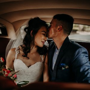 A couple kissing inside of a classic car on their wedding day
