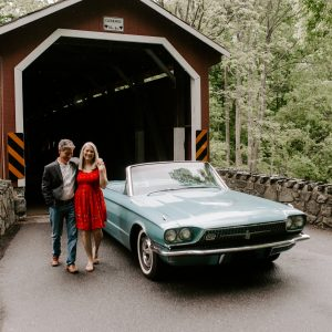 A couple smiling in front of a turquoise classic car on a covered bridge in Lancaster, PA